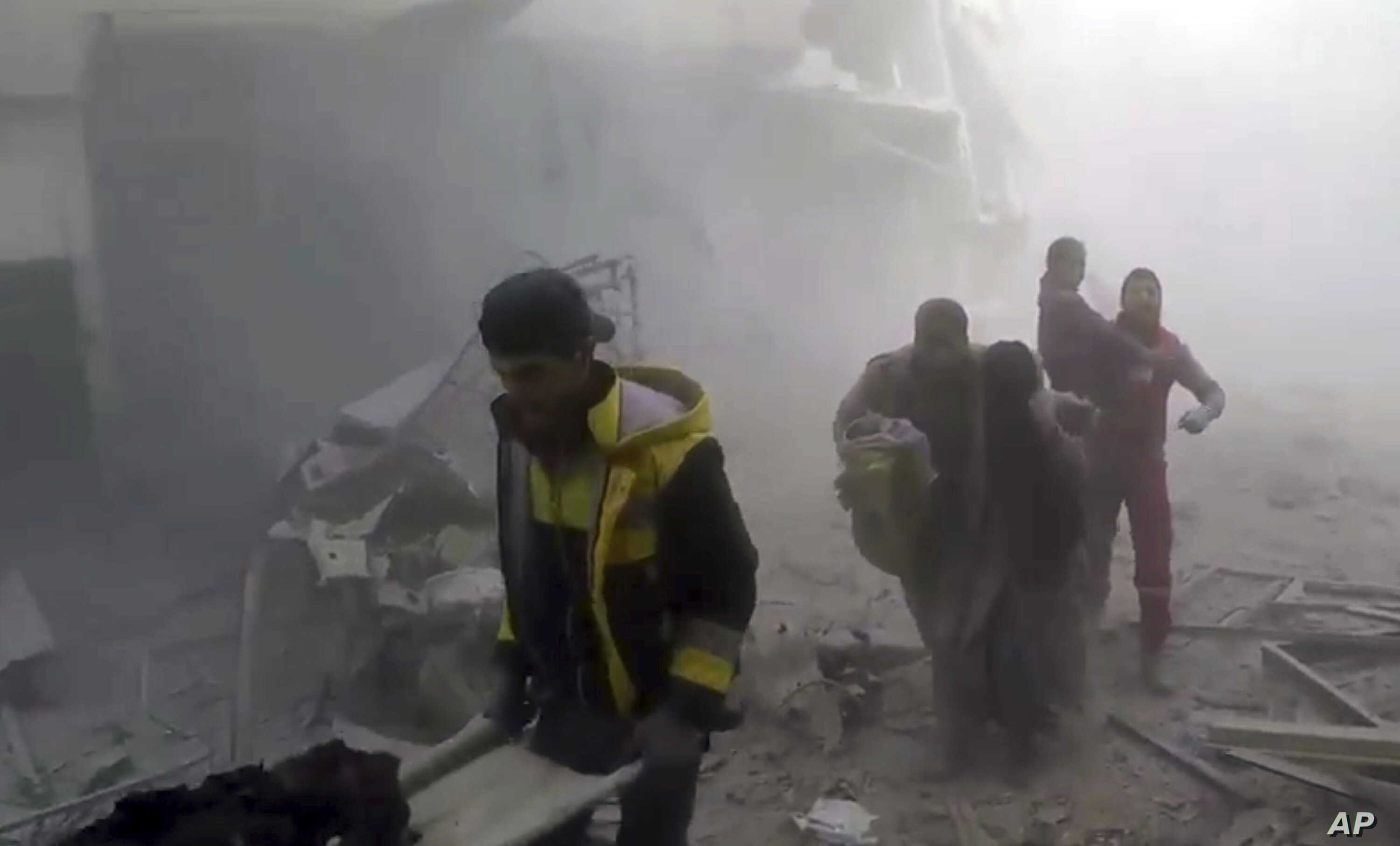 This frame grab from video released Feb 24, 2018, by the Syrian civil defense group known as the White Helmets shows members of the group helping residents during airstrikes and shelling by Syrian government forces, in Ghouta, a suburb of Damascus, S...