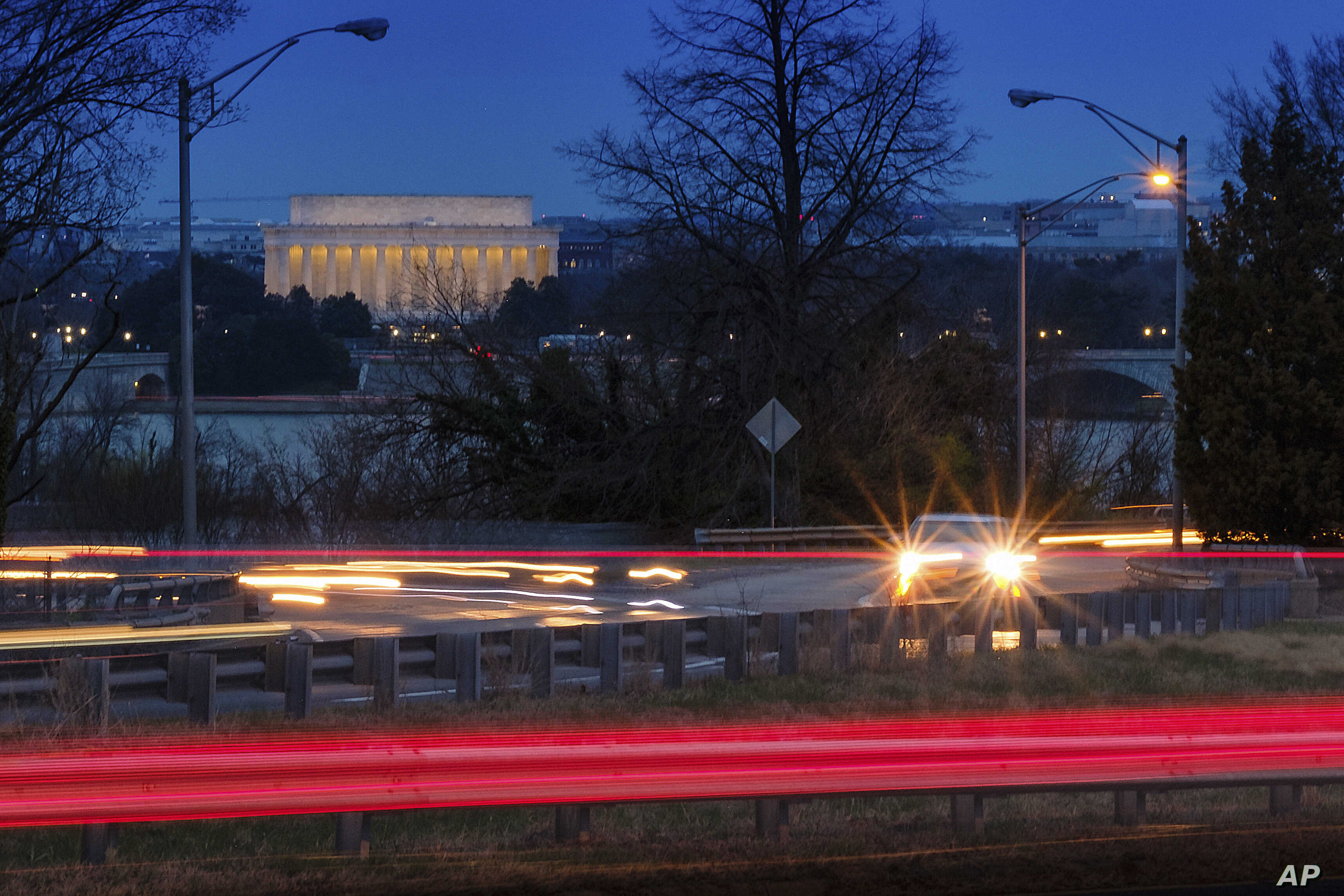 FILE - Traffic streaks along U.S. Highway 50 early in the morning, March 30, 2018, in Arlington, Va. The Trump administration announced April 2, 2018, that it would revise tough mileage standards for cars and light trucks, saying Obama-era rules were...