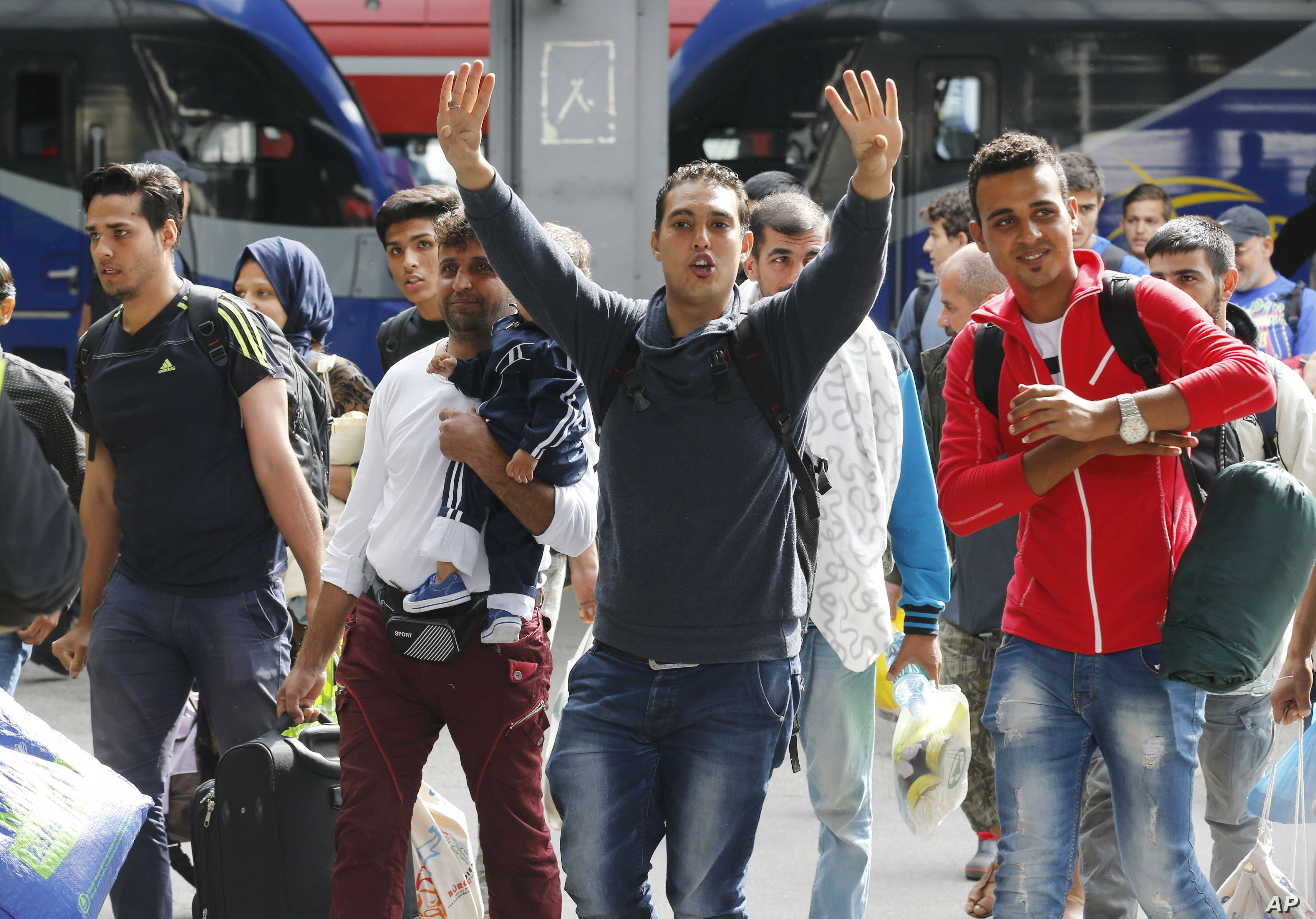 Refugees wave as they arrive at the main train station in Munich, Germany, Sept. 5, 2015.