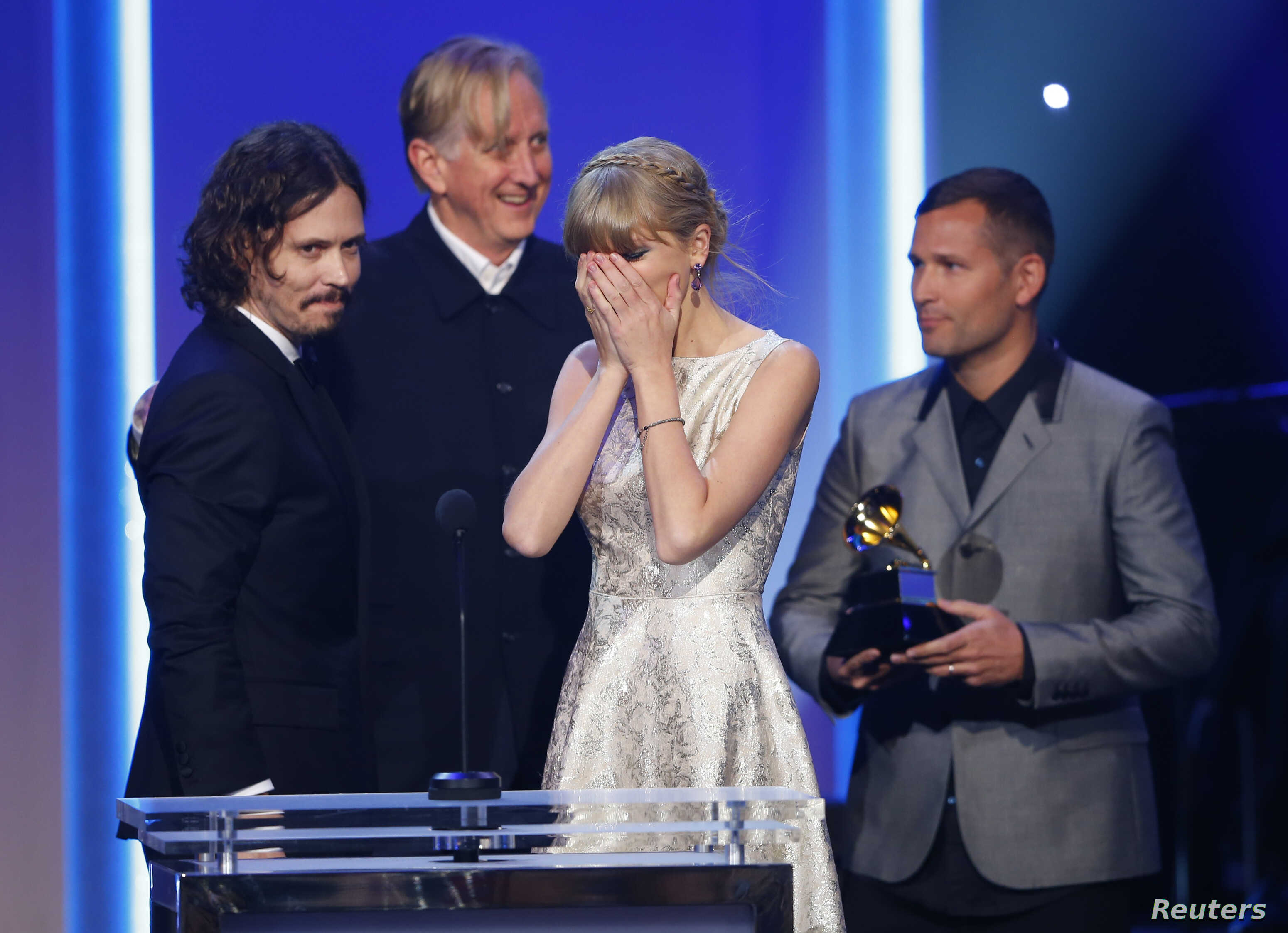 """Singer Taylor Swift reacts as she accepts the Grammy award for Best Song Written For Visual Media for """"Safe & Sound"""" with John Paul White (L) and T Bone Burnett (2nd from L) at the 55th annual Grammy Awards in Los Angeles, California, February 10, 20"""