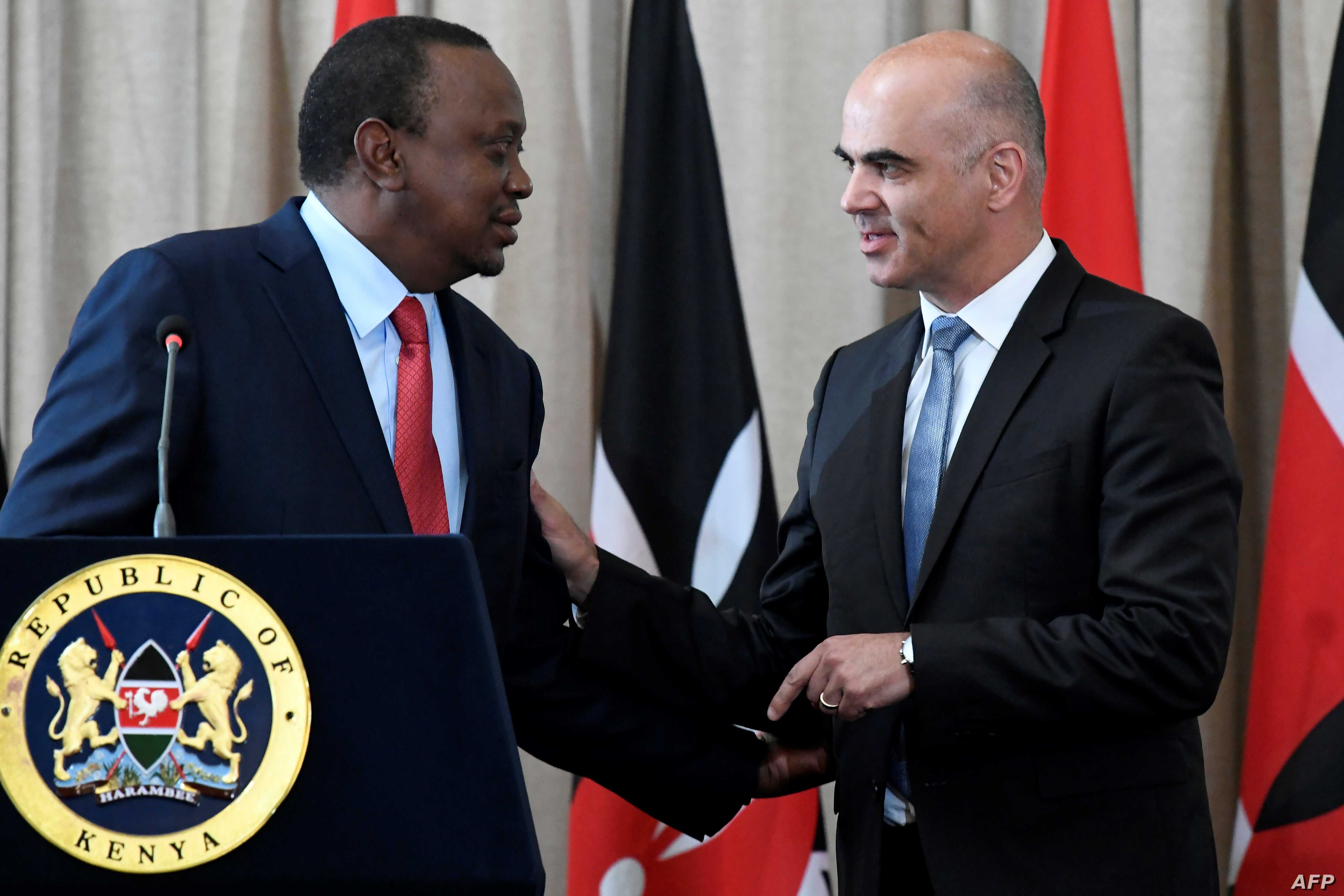Swiss President Alain Berset (R) speaks with his Kenyan counterpart President Uhuru Kenyatta during a joint press conference at the State House in Nairobi, July 9, 2018, during Berset's official visit.