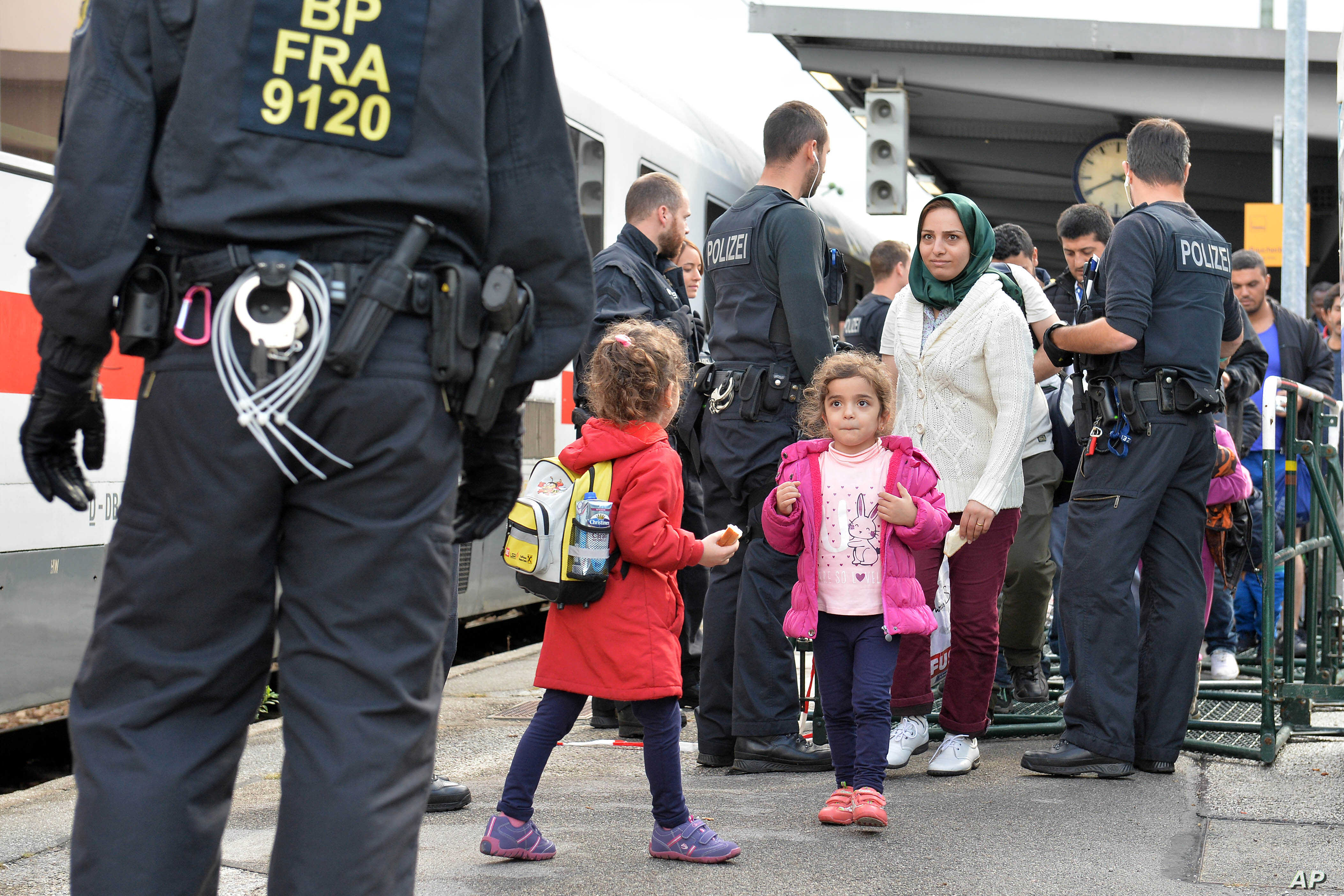 Refugees wait for a train at the rail station in Freilassing, southern Germany, near the Austrian border, Sept. 18, 2015.