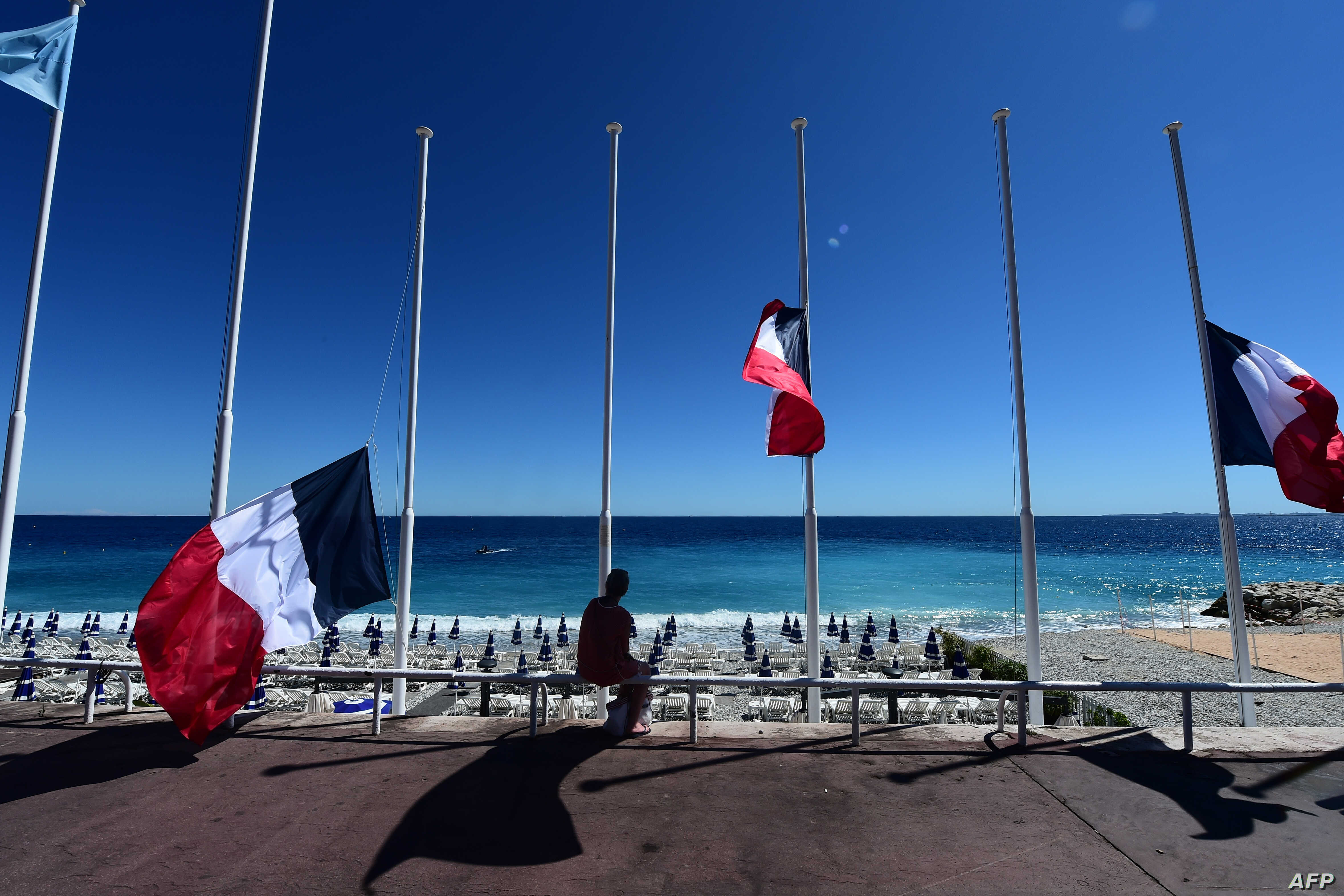 A woman sits under French flags lowered at half-mast in Nice on July 15, 2016, following the deadly Bastille Day attacks.