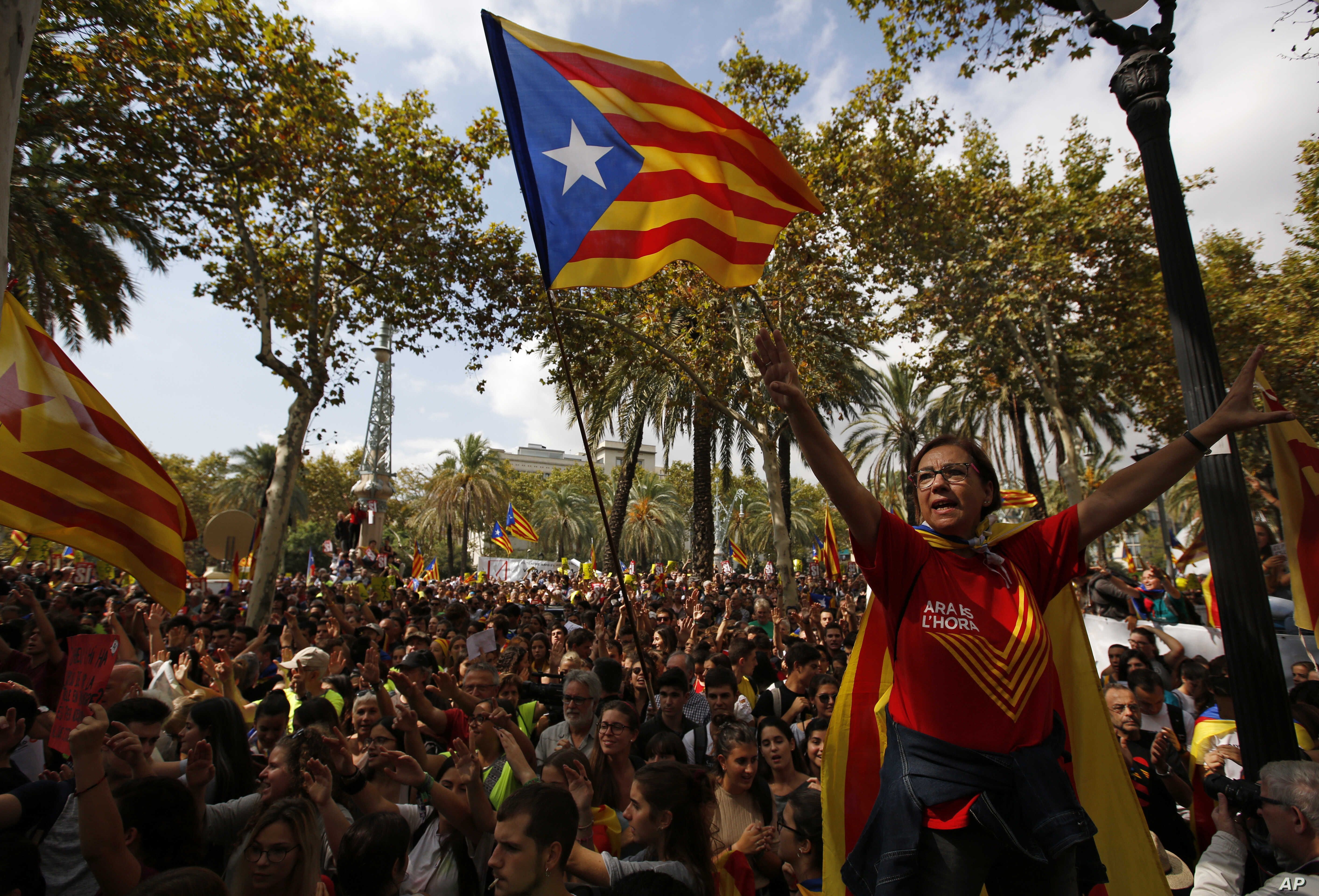 A woman gestures as others wave the ''estelada'' or Catalonia independence flags during a protest in Barcelona, Spain, Sept. 21, 2017.