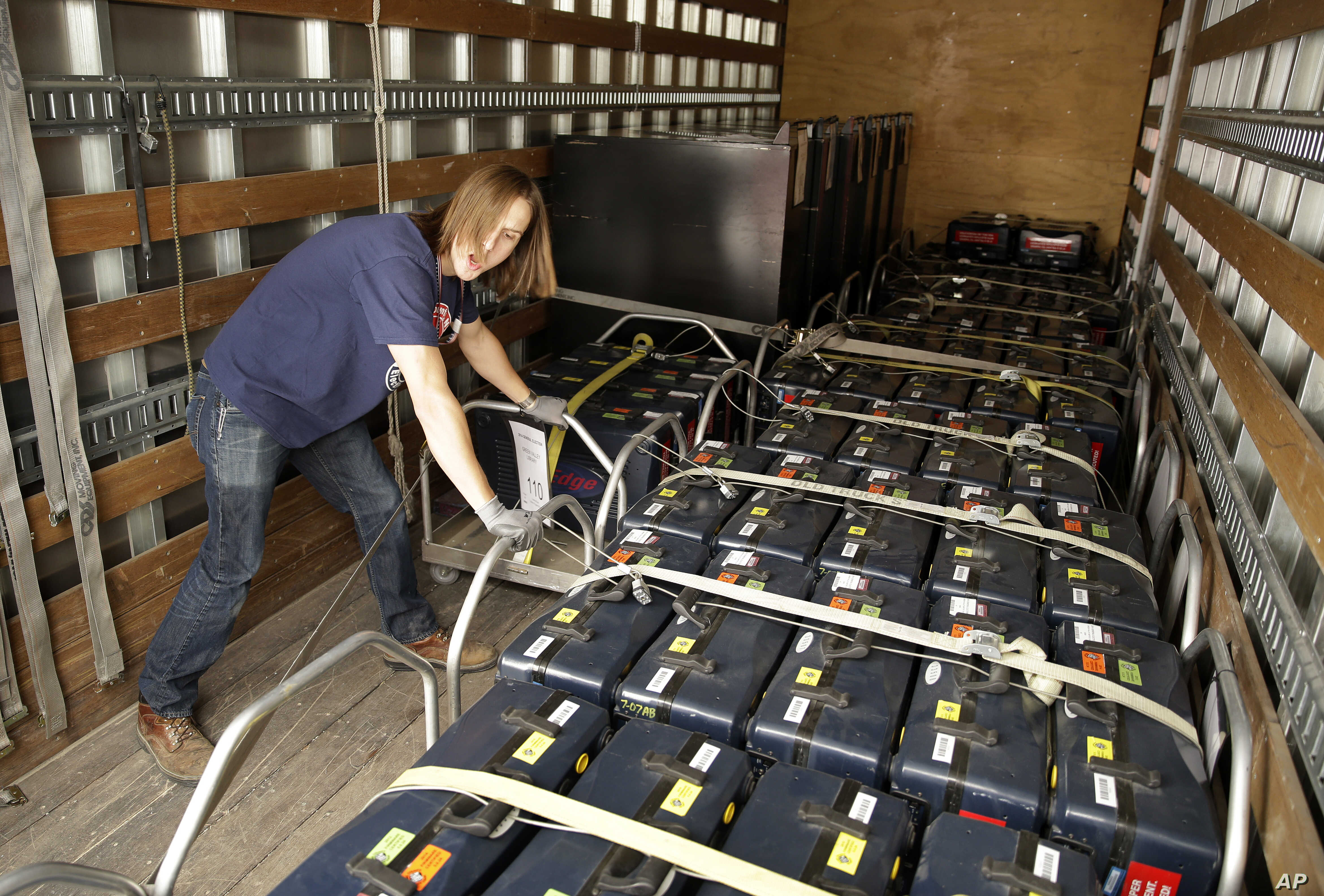 Clark County election worker Bradley Kryst loads voting machines onto a truck at the Clark County Election Warehouse Monday, Nov. 3, 2014, in North Las Vegas, Nev. The machines will be used for midterm elections on Tuesday. (AP Photo/John Locher)