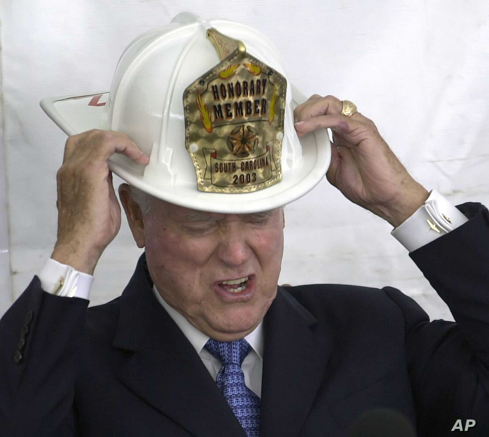 FILE - Sen. Ernest Hollings, D-S.C., puts on a firefighter helmet after he was awarded an honorary membership in the South Carolina Firemen's Association during a luncheon April 22, 2003, in Columbia, S.C.