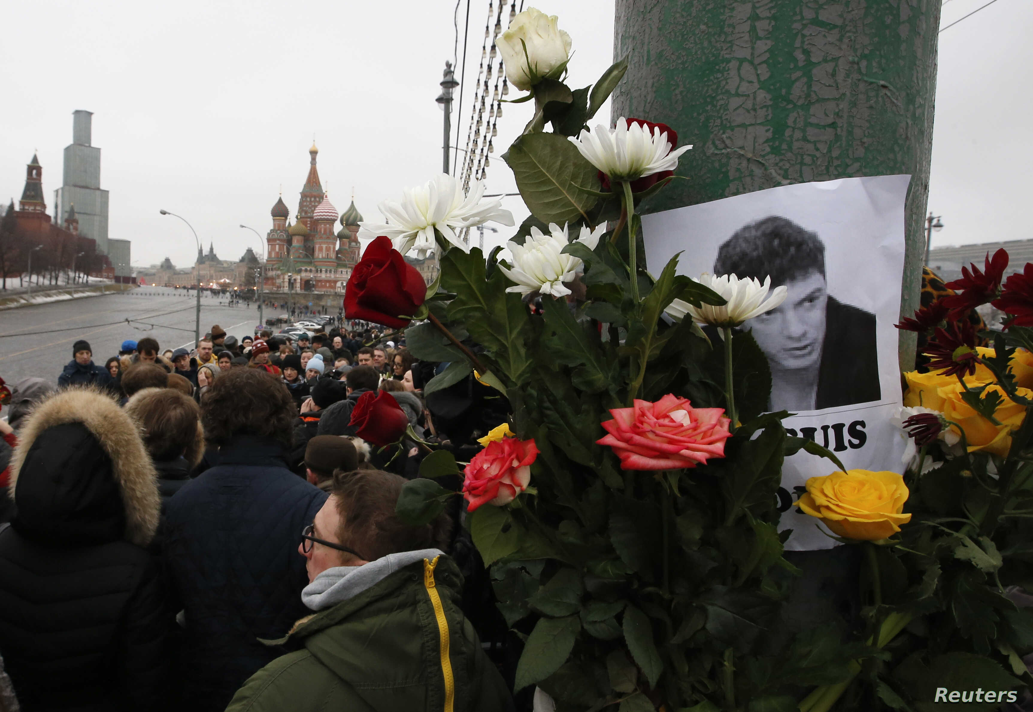 People gather at the site where Boris Nemtsov was recently murdered, with St. Basil's Cathedral and the Kremlin seen in the background, in central Moscow, February 28, 2015. Russia's Investigative Committee is pursuing several lines on inquiry follow...