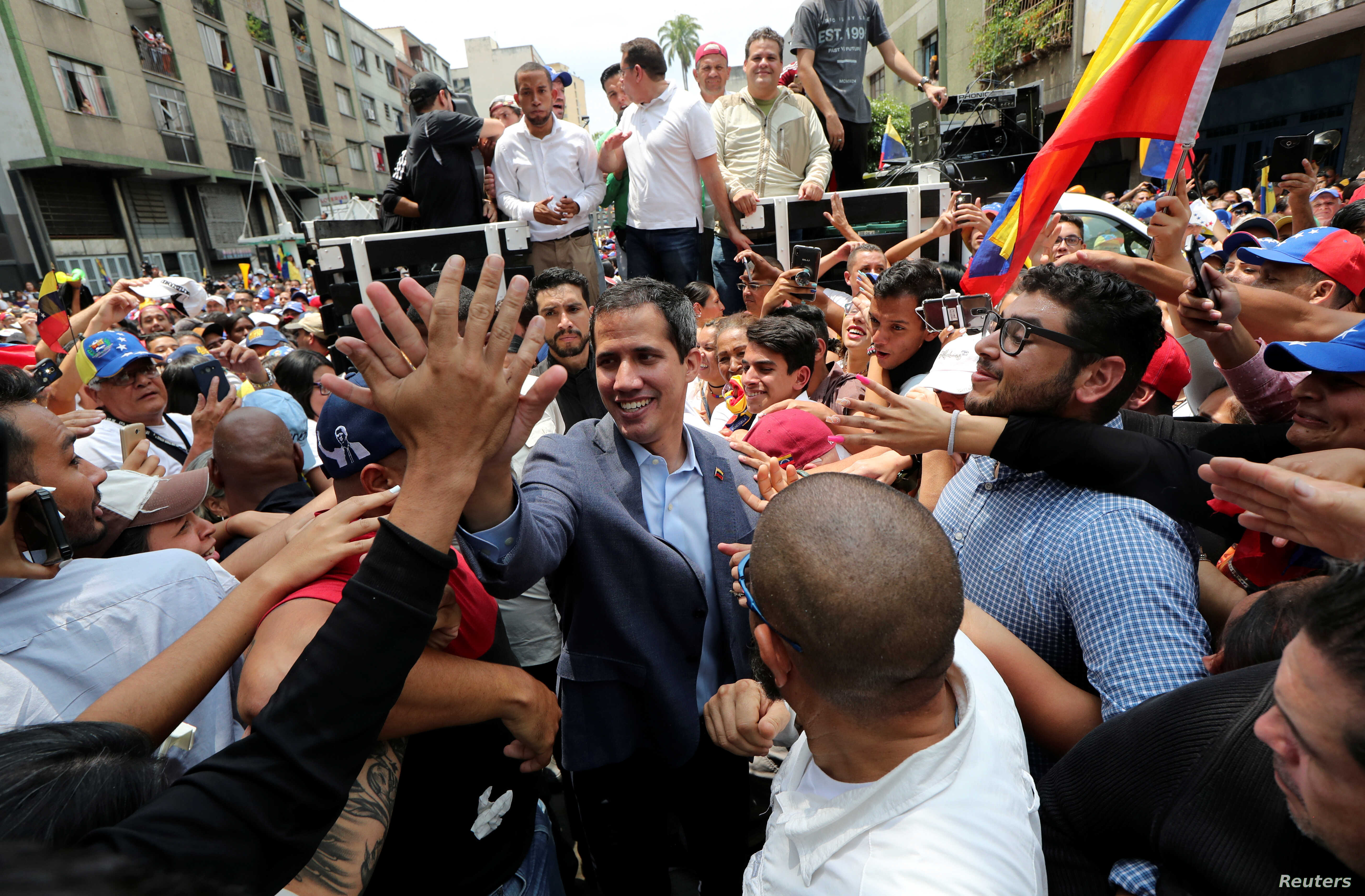 Venezuelan opposition leader Juan Guaido, whom many nations have recognized as the country's rightful interim ruler, greets supporters during a rally in Los Teques, Venezuela, March 30, 2019.