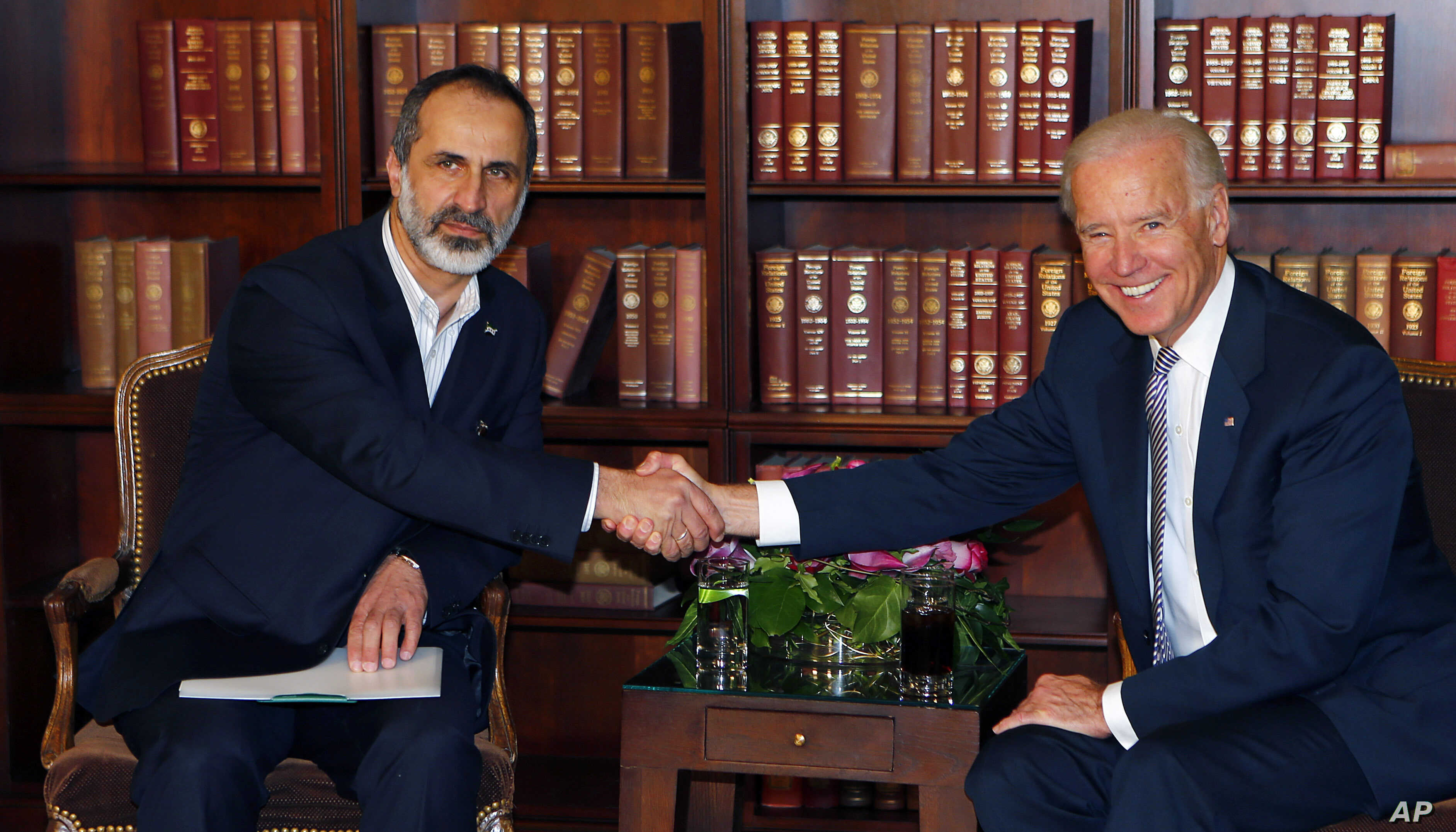 US Vice President Joe Biden, right, and Sheikh Moaz al-Khatib, Syria's  top opposition leader, shake hands at the Security Conference in Munich, Germany, February 2, 2013.