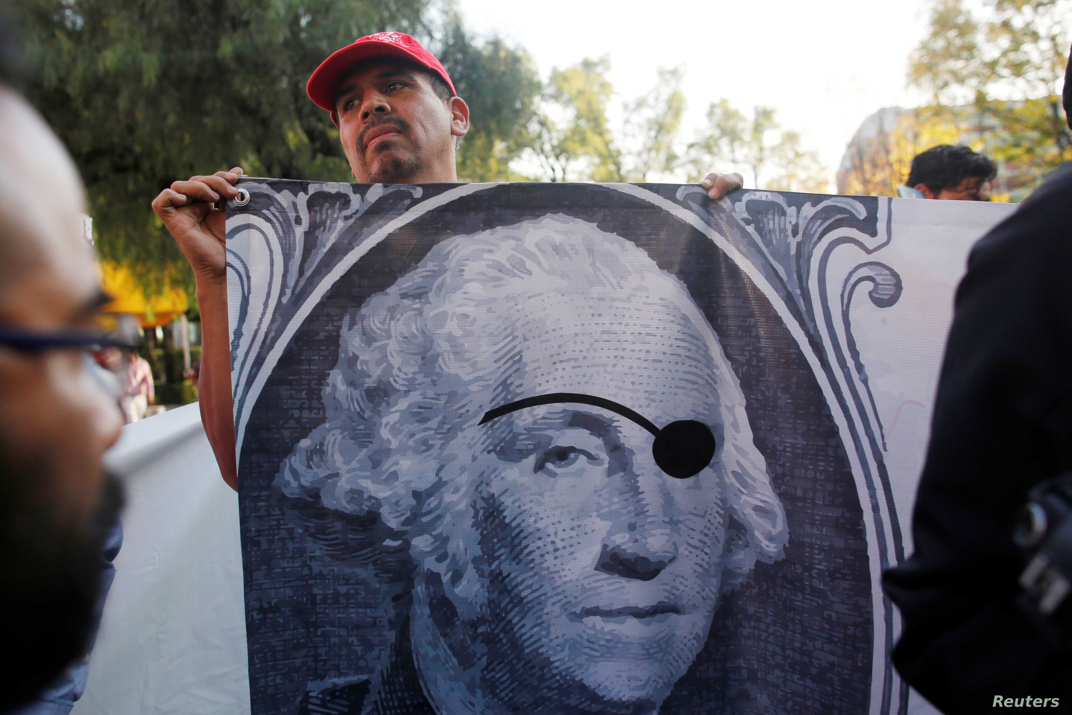 A union worker holds a banner during a protest against NAFTA negotiations outside the site of the fifth round of NAFTA talks involving the United States, Mexico and Canada in Mexico City, Nov. 17, 2017.