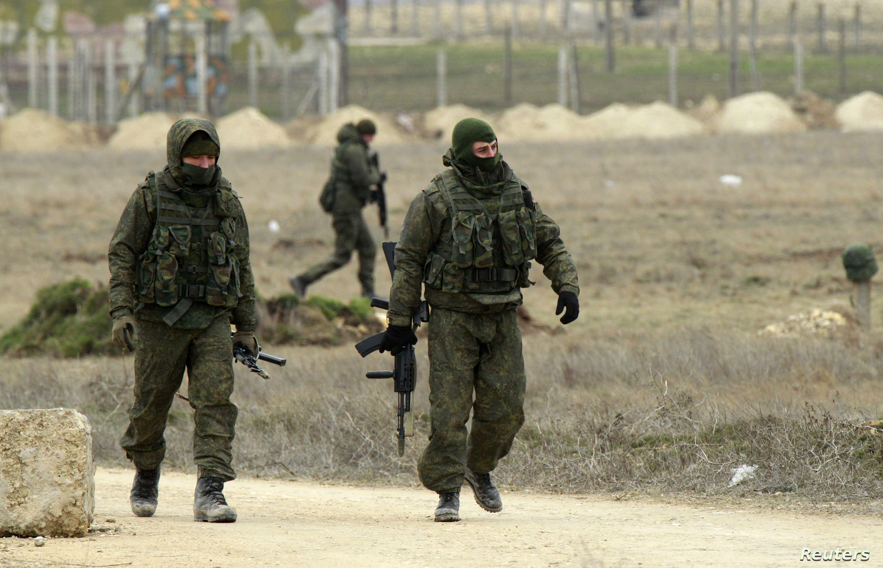 FILE - Armed men, believed to be Russian soldiers, are seen walking at the Crimean port of Yevpatoriya March 8, 2014.