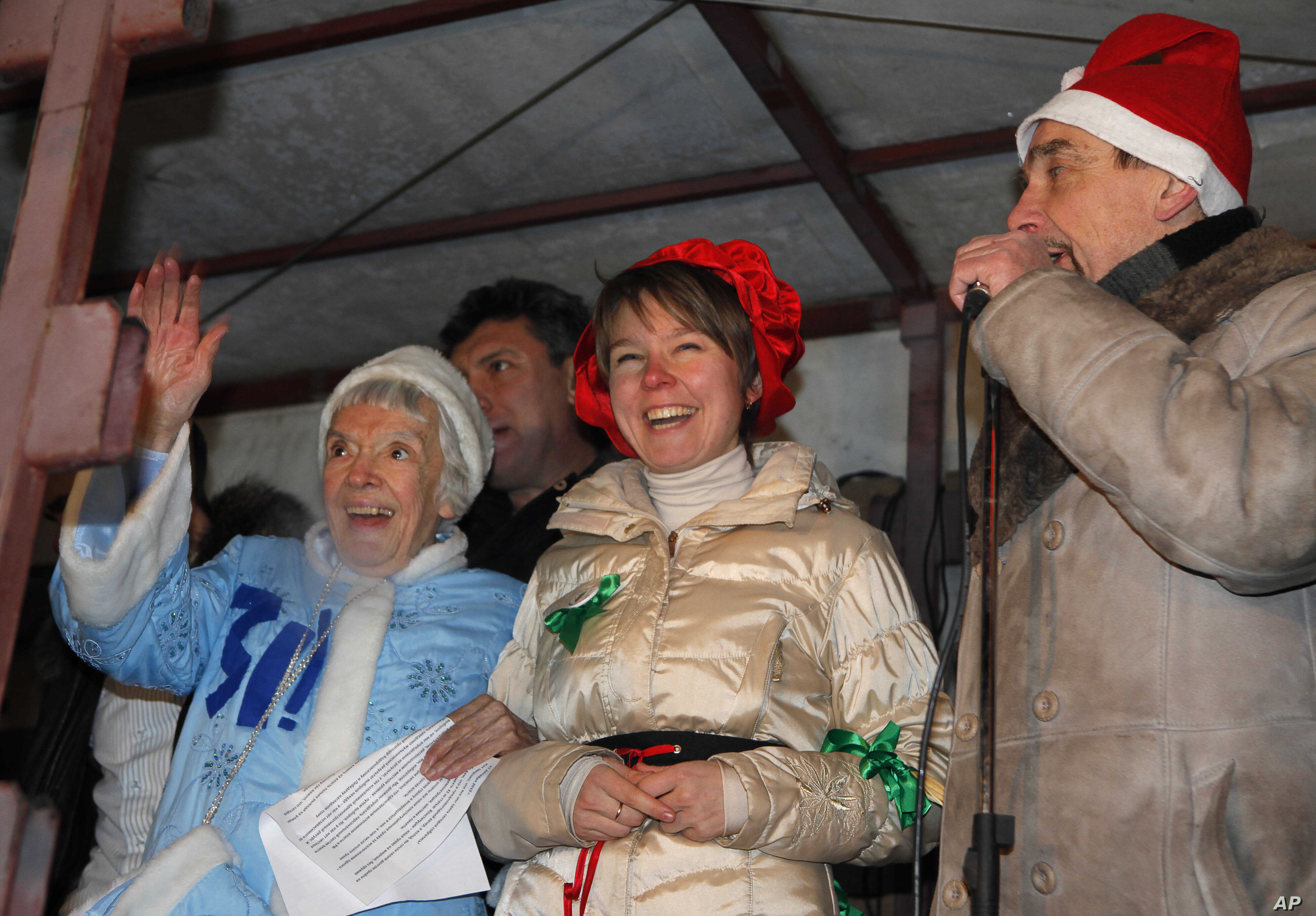 FILE - Russian human rights activist Lyudmila Alexeyeva, dressed as Snegurochka, Russian Snow Maiden, left, environmental activist Yevgenia Chirikova, center, and  prominent rights activist Lev Ponomaryov speak during a rally in central Moscow, Dec. ...