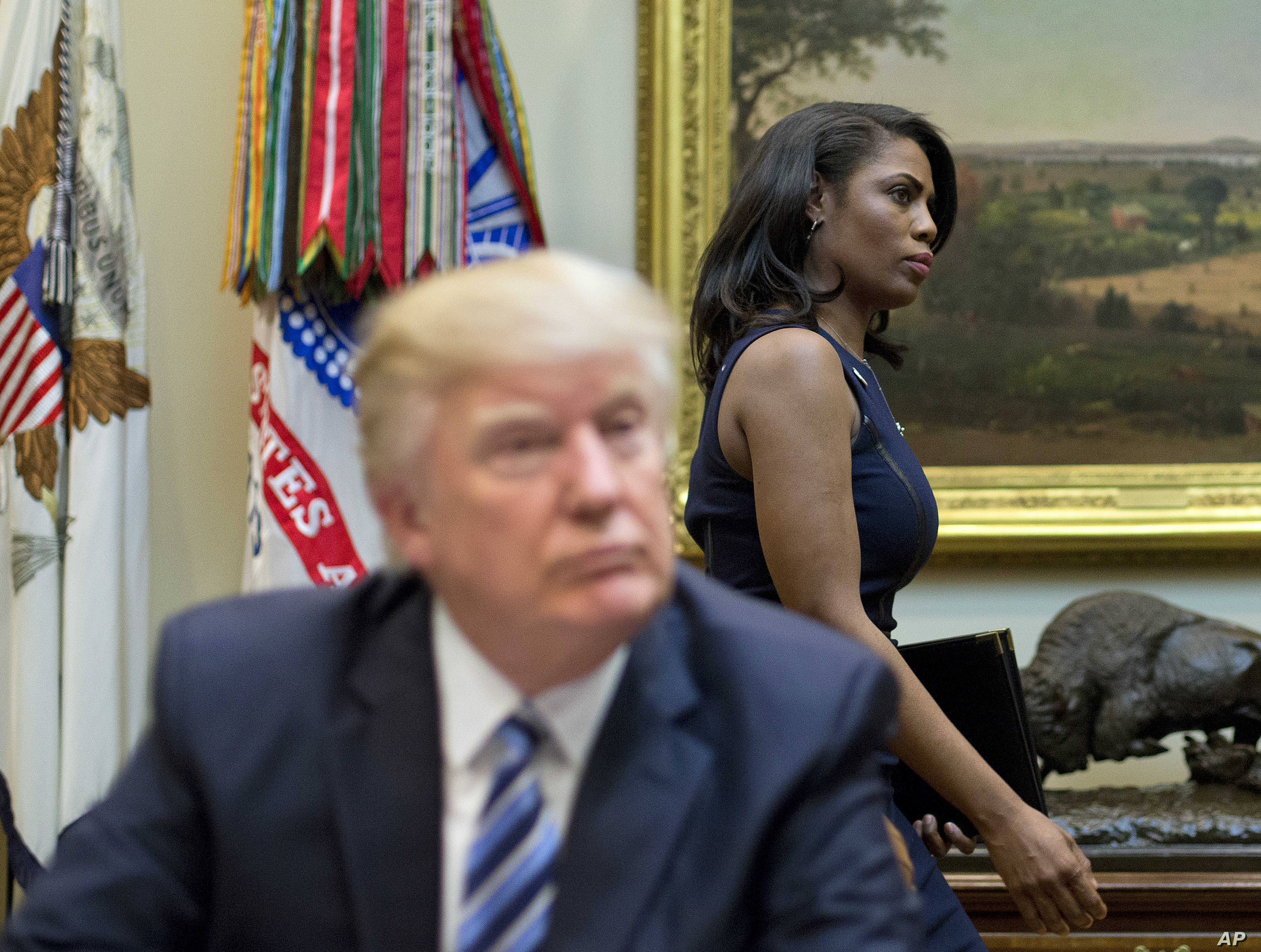 FILE - In this March 12, 2017 file photo, White House Director of communications for the Office of Public Liaison Omarosa Manigault, right, walks past President Donald Trump during a meeting on healthcare in the White House.