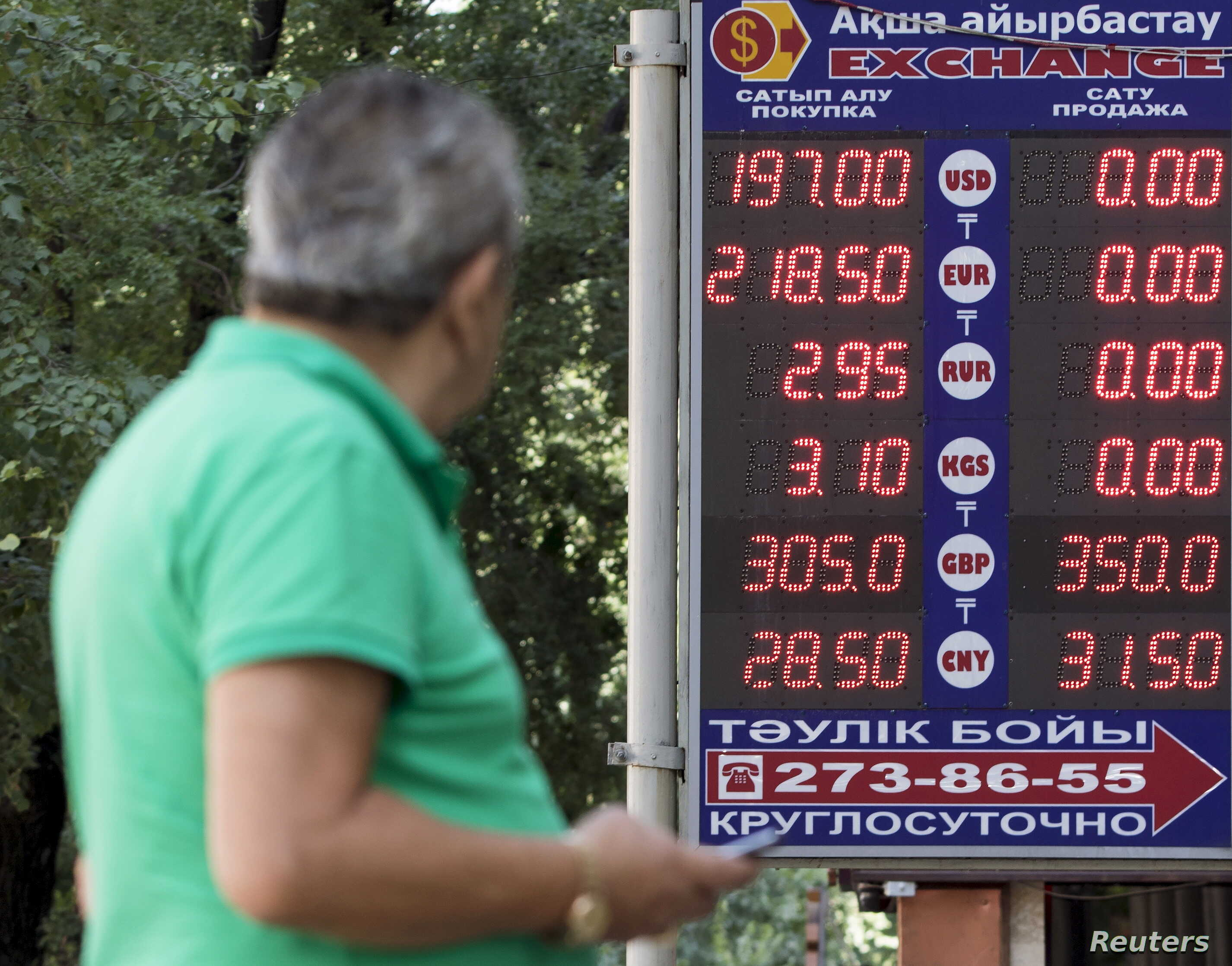 A man uses his mobile phone as he walks past a board showing currency exchange rates in Almaty, Kazakhstan, Aug. 20, 2015.
