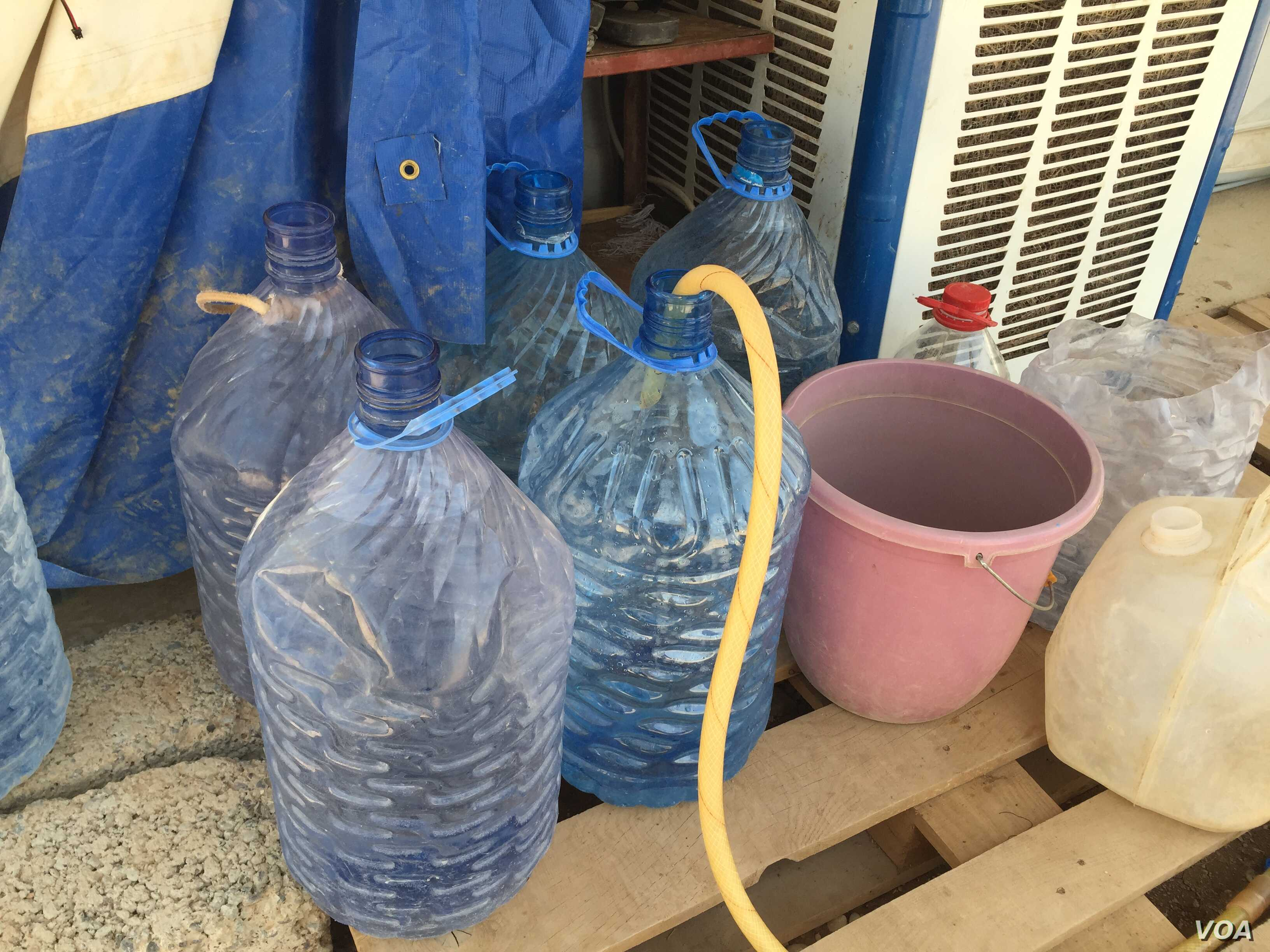 """Filling up water bottles in the Baharka camp on the outskirts of Irbil, in the Kurdistan region of Iraq. Considered a """"five-star"""" camp, Baharka houses some 4,000 people, half of whom are teenagers, Aug 5, 2015 (VOA photo - Sharon Behn)."""