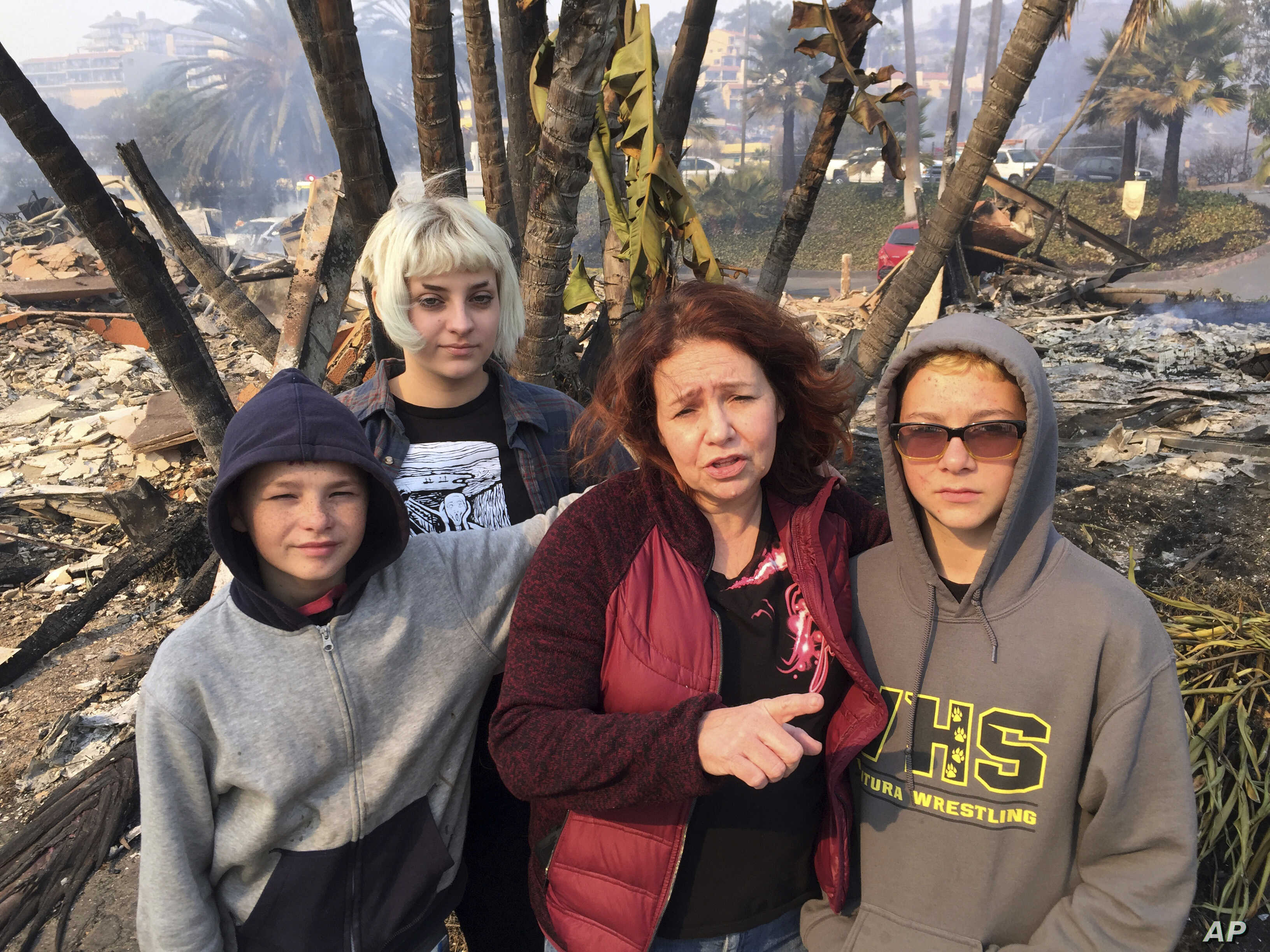 Lisa Kermode, second from right, and her children, from left, Damien, Lola and Michael, stand outside the ruins of their home after a wildfire swept through Ventura, Calif., Dec. 5, 2017. They were home Monday night when Lisa started to smell smoke a...