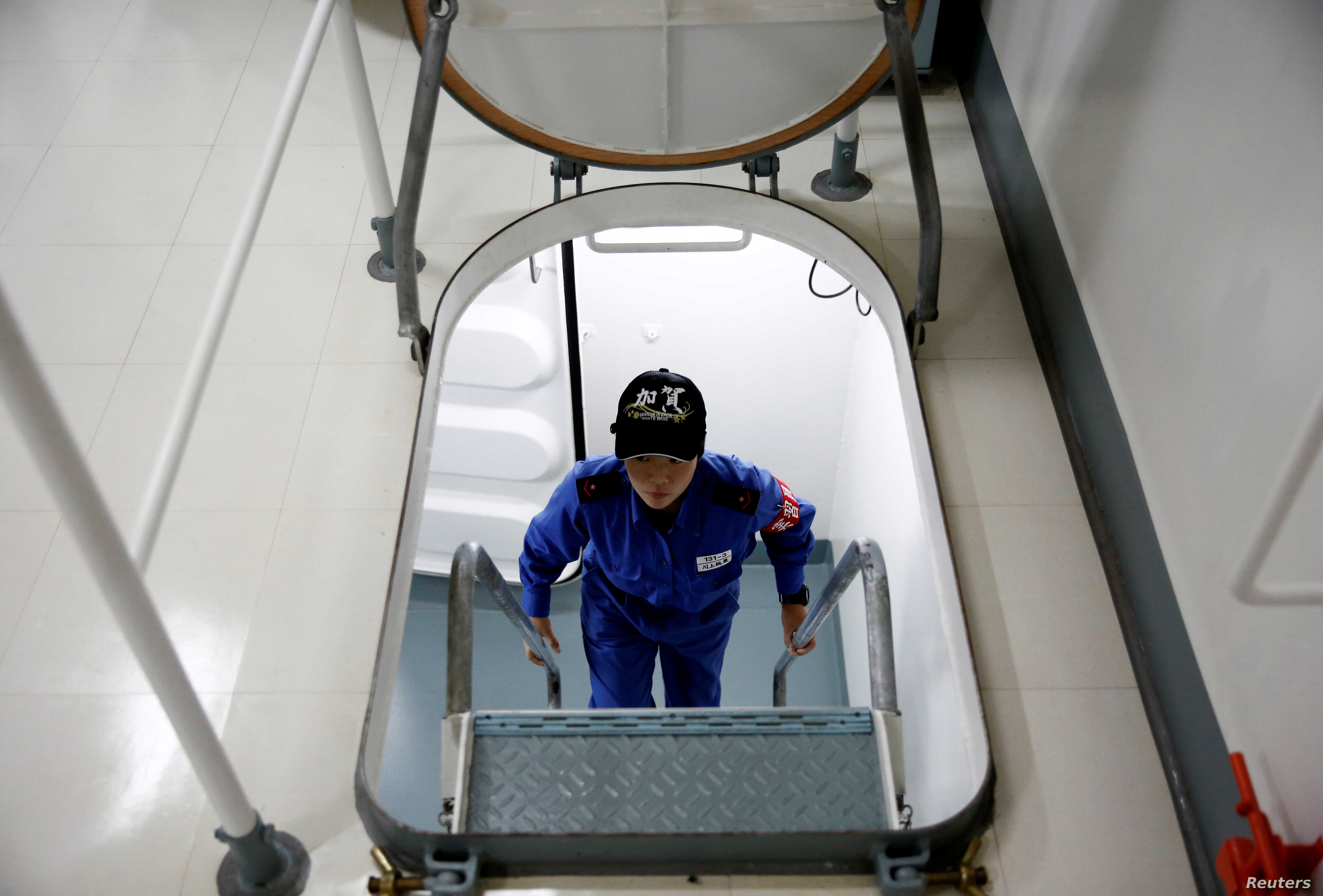 A female trainee climbs a ladder as she makes her way to a class aboard the Japanese helicopter carrier Kaga in the Indian Ocean, Indonesia, Sept. 23, 2018.