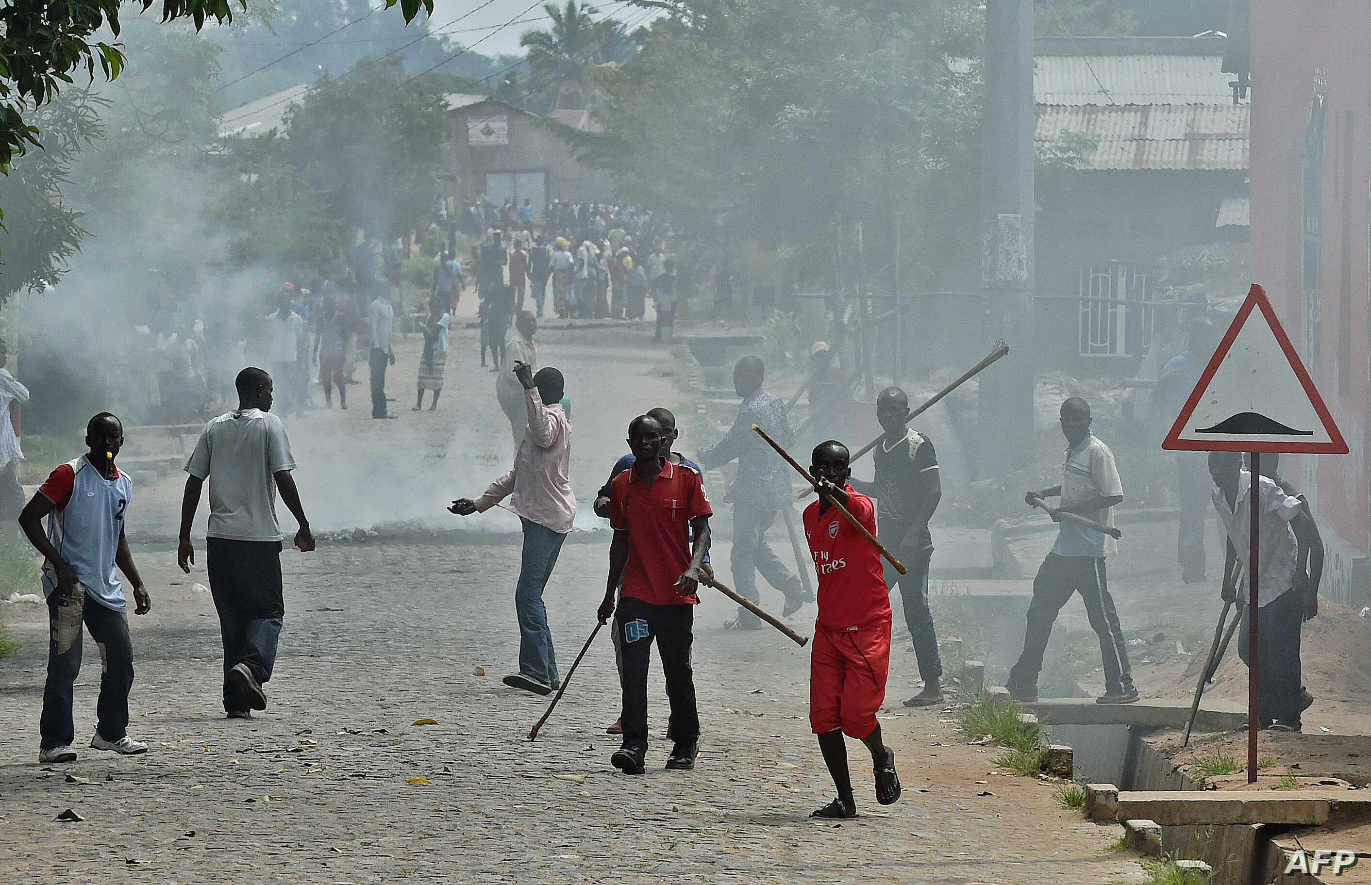 FILE - Members of the Imbonerakure, armed with sticks, chase protesters opposed to the Burundian president's third term in the Kinama neighborhood of Bujumbura, May 25, 2015.