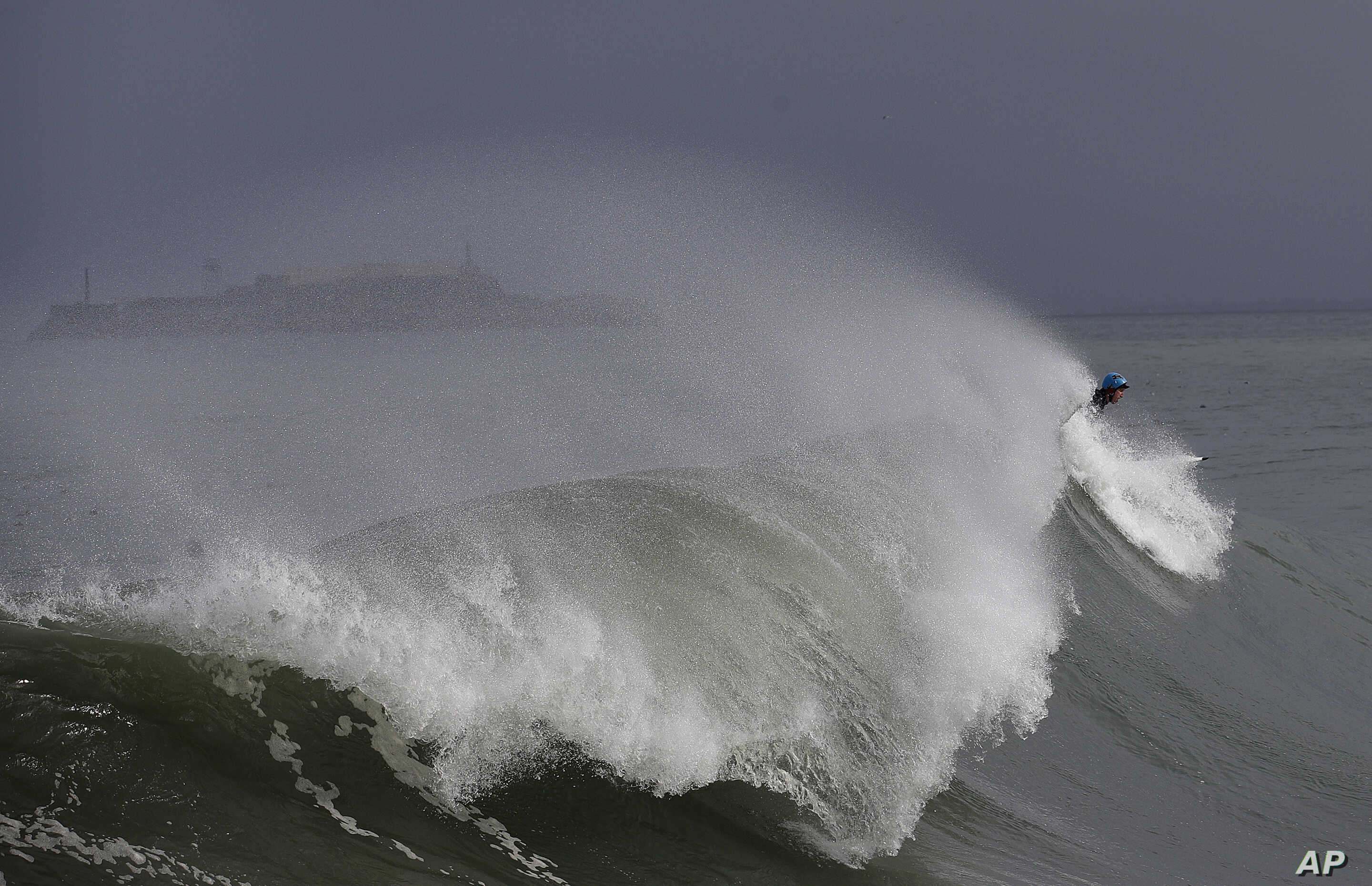 A  surfer rides a wave near Fort Point in front of Alcatraz Island in San Francisco, , Nov. 29, 2018. A storm moving into California brought rain that may bring snow and cause travel problems in the Sierra Nevada mountains.