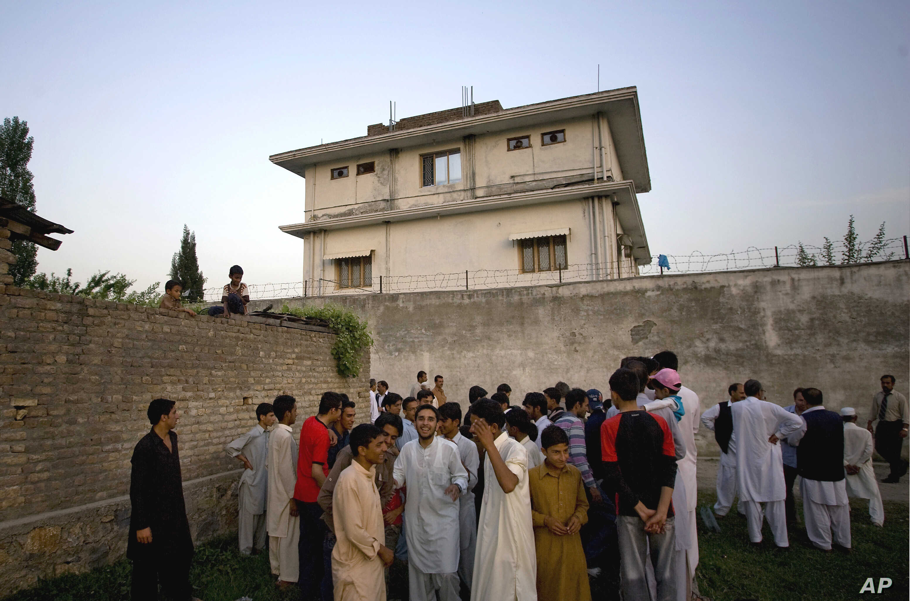 FILE - In this May 3, 2011, photo, local residents gather outside a compound where al-Qaida leader Osama bin Laden was killed by U.S. forces, in Abbottabad, Pakistan.