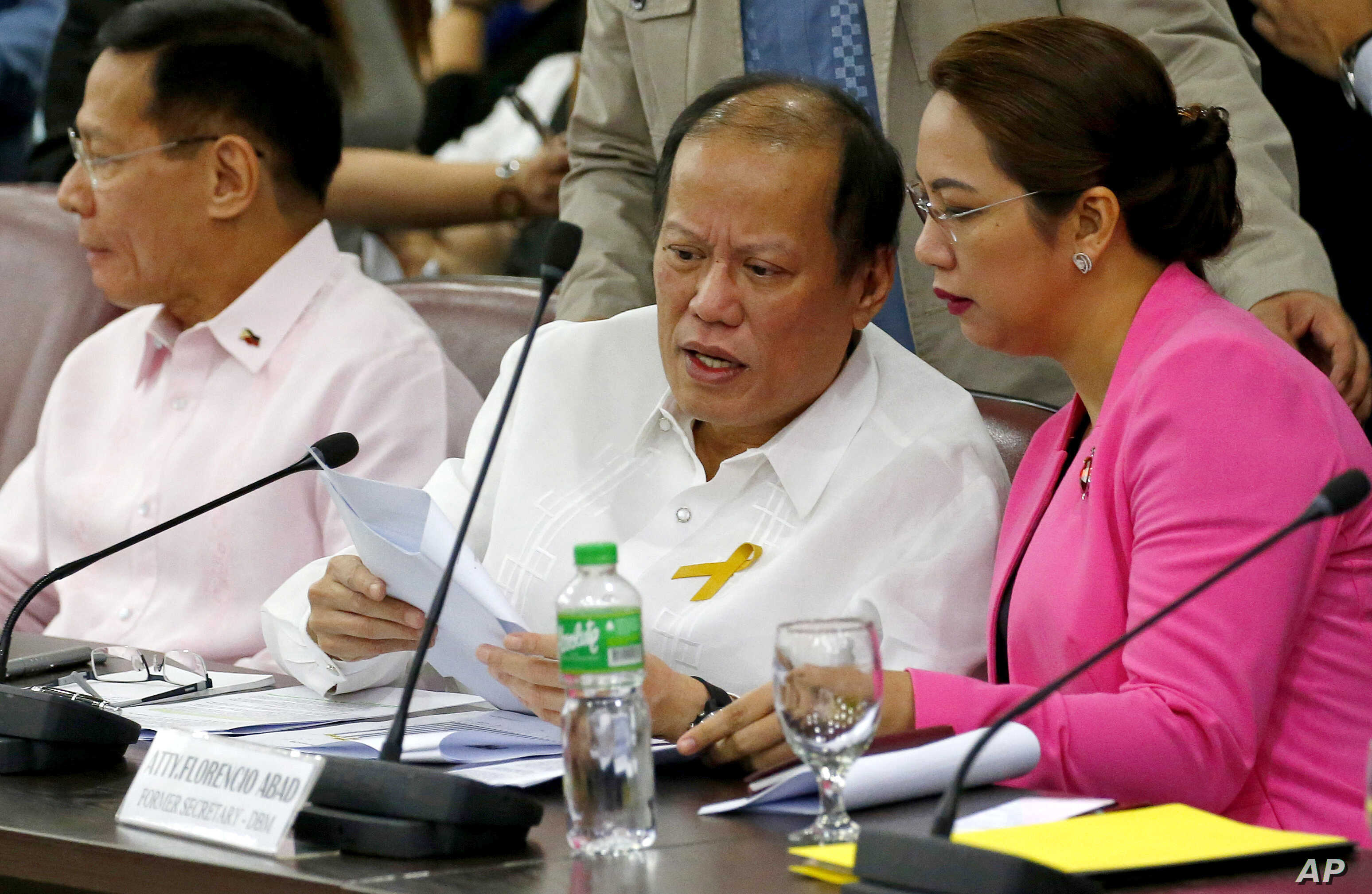Former Philippine President Benigno Aquino III, center, confers with former Health Secretary Janet Garin as they both testify in a separate Lower House probe on the controversial anti-Dengue vaccine Dengvaxia, Feb. 26, 2018 in suburban Quezon city no...