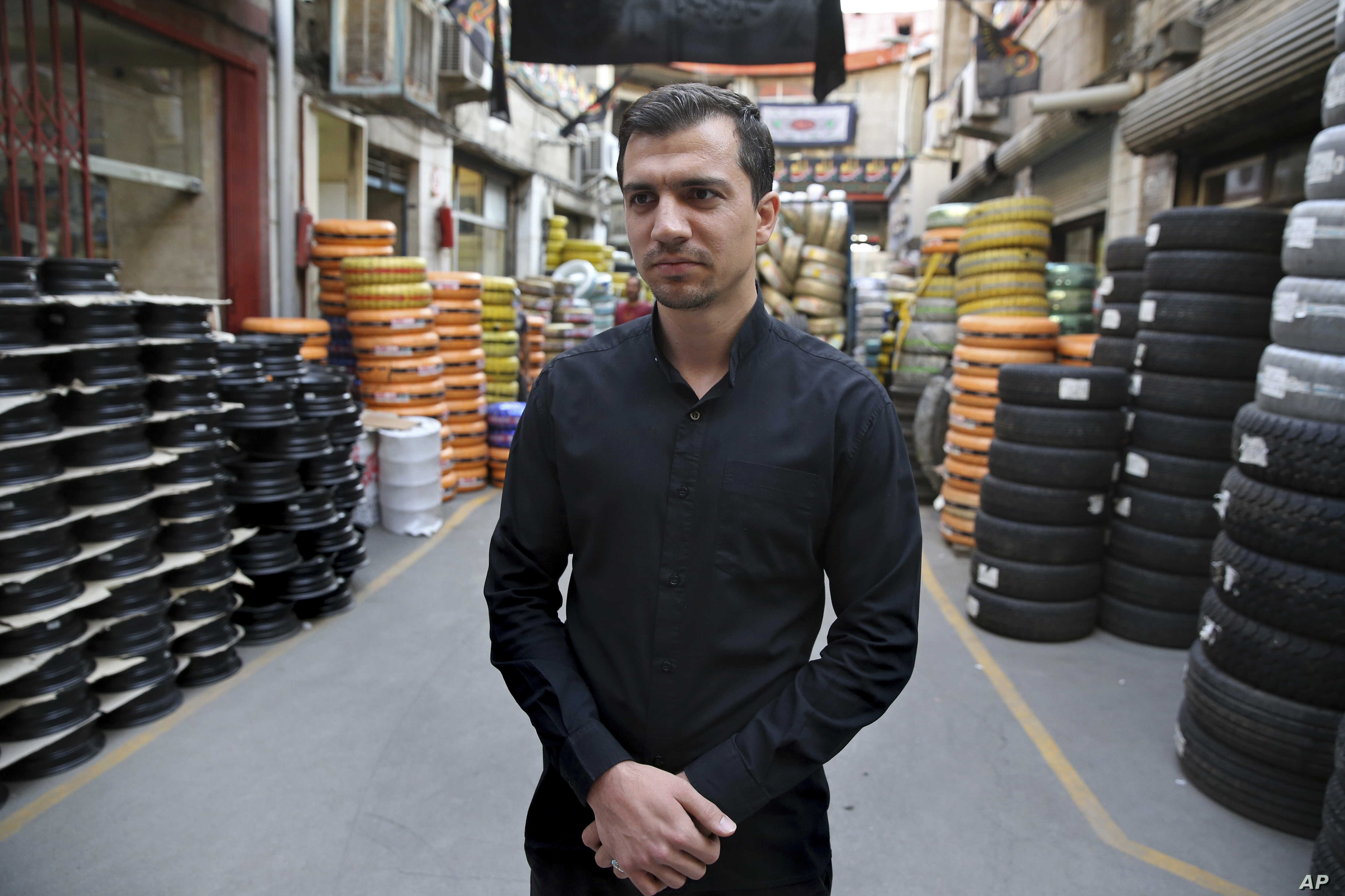 Mehdi Abedi, a 30-year-old tire dealer, speaks at a market, in downtown Tehran, Iran, Oct. 8, 2017.