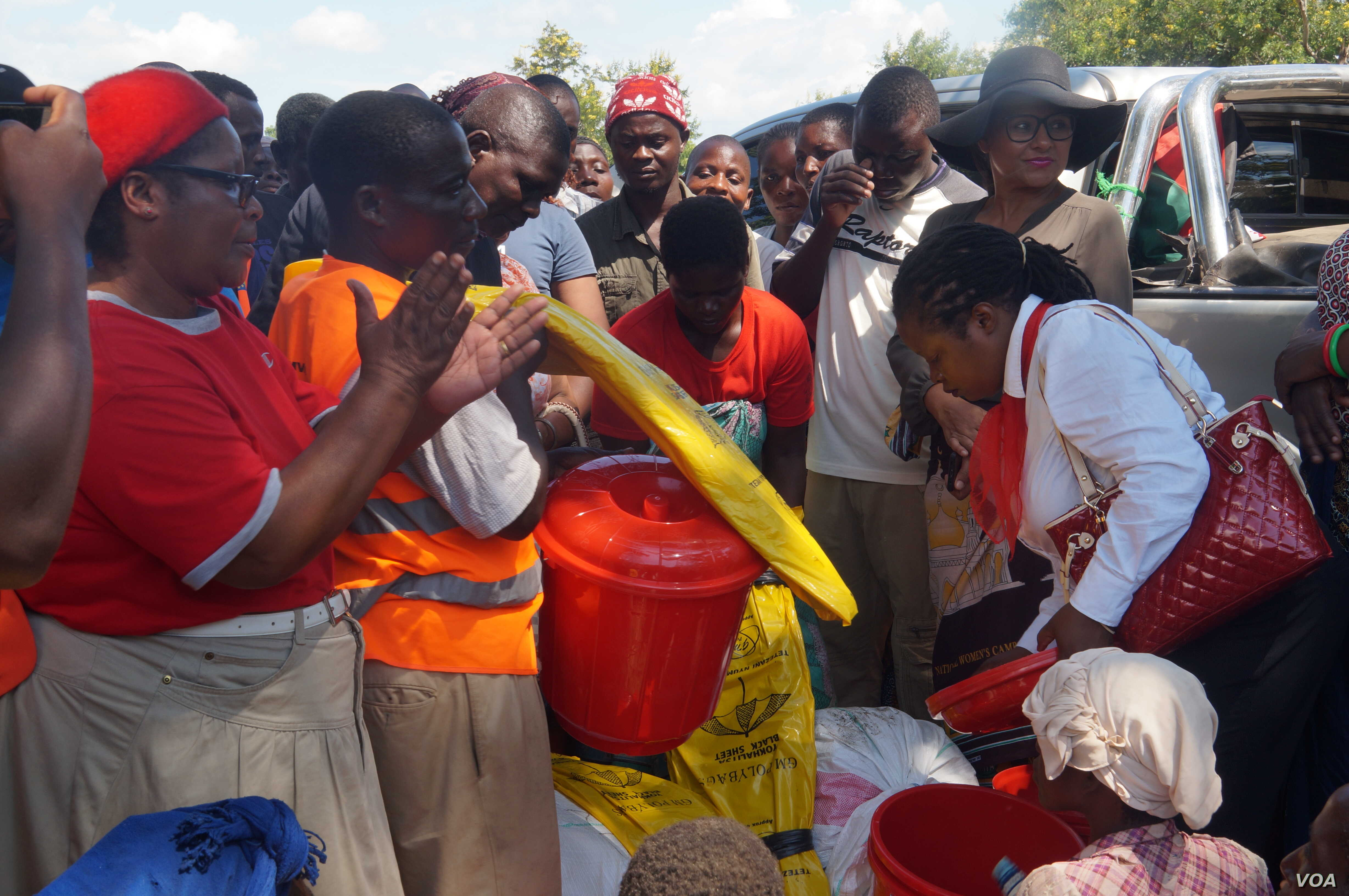 Due to erratic donor aid, local well-wishers are coming in to help flood victims with whatever they can provide. (L. Mesina for VOA)