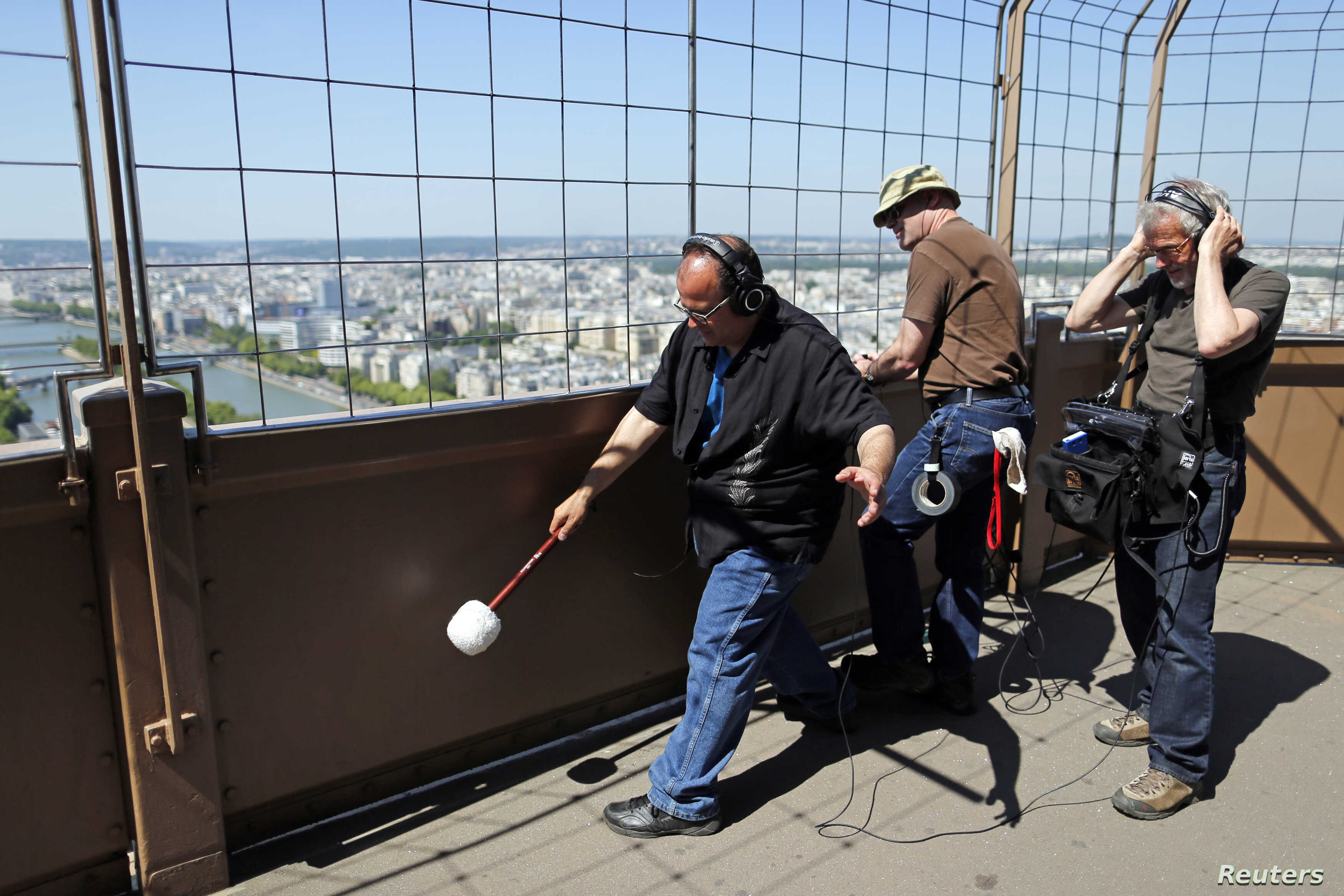 U.S. composer Joseph Bertolozzi (L) makes sounds by striking the surface of the Eiffel Tower for a musical project called 'Tower music' in Paris June 7, 2013. Bertolozzi and his team collect sounds with a microphone to use them as samples for their c...