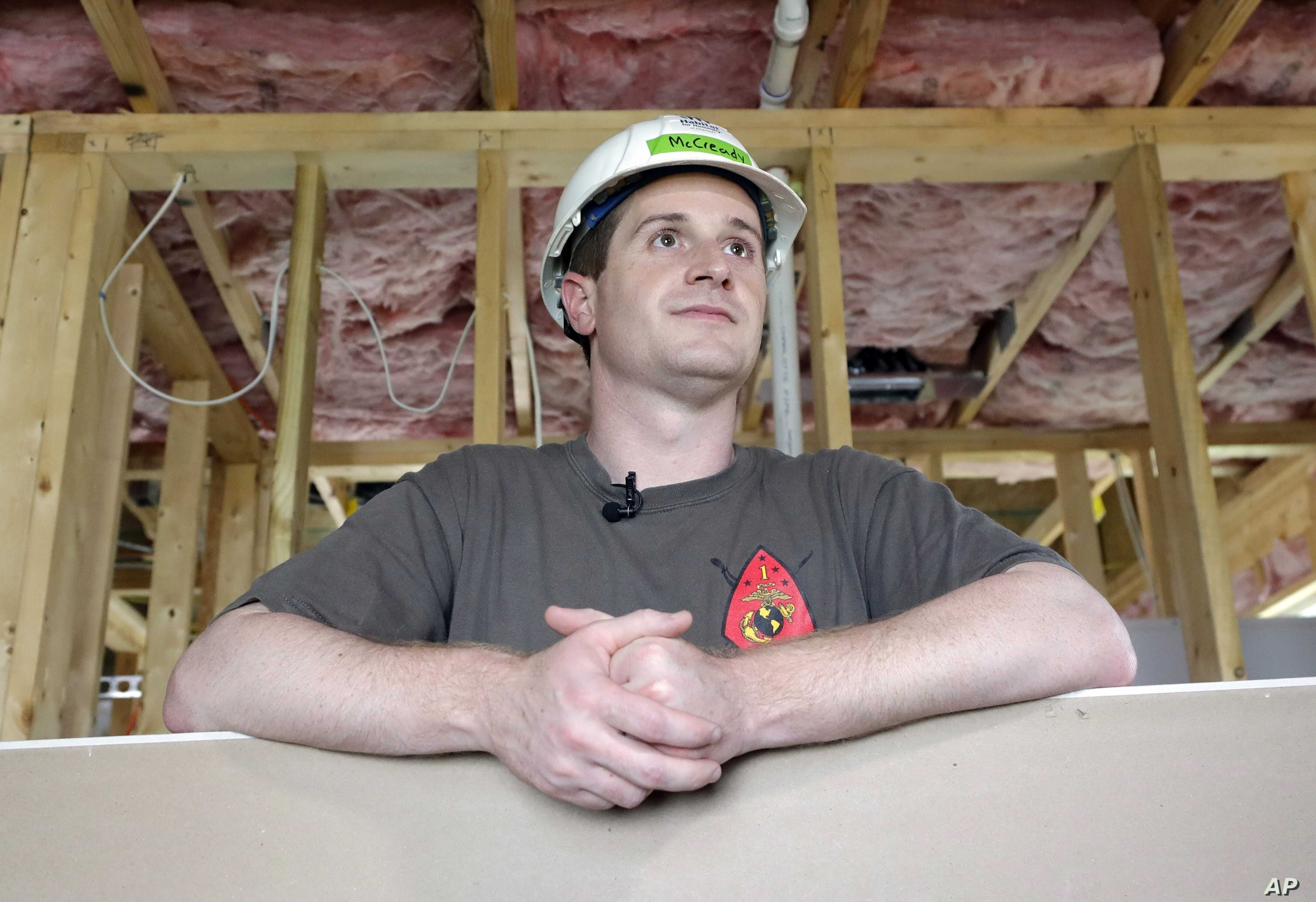 FILE - In this Sept. 26, 2018, file photo, Democratic congressional candidate Dan McCready leans against wallboard as he pauses during a Habitat For Humanity building event in Charlotte, North Carolina.