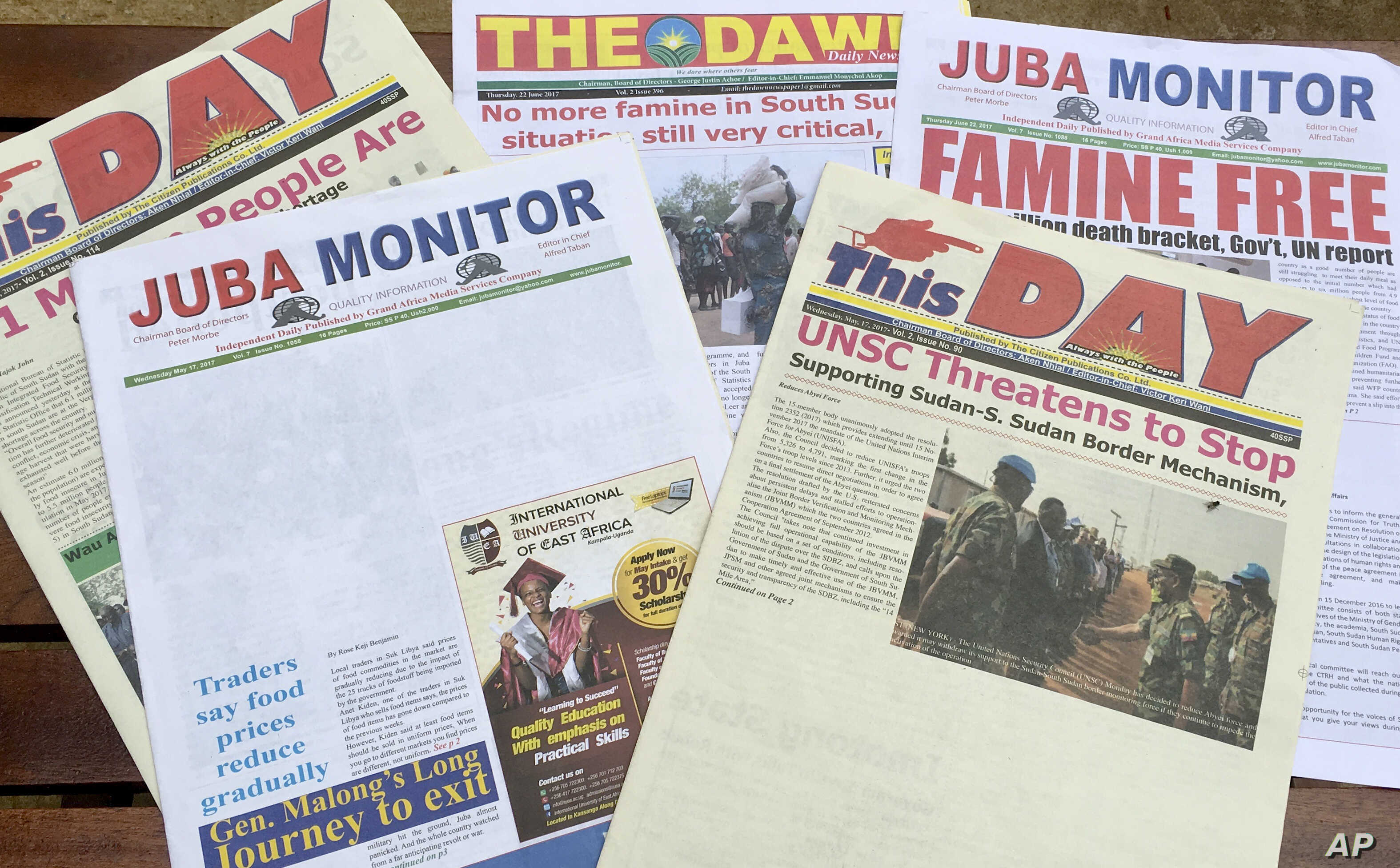 This photo taken June 22, 2017 shows South Sudanese newspaper front pages, including two with news stories removed by the printer on the instructions of the government, in Juba, South Sudan.
