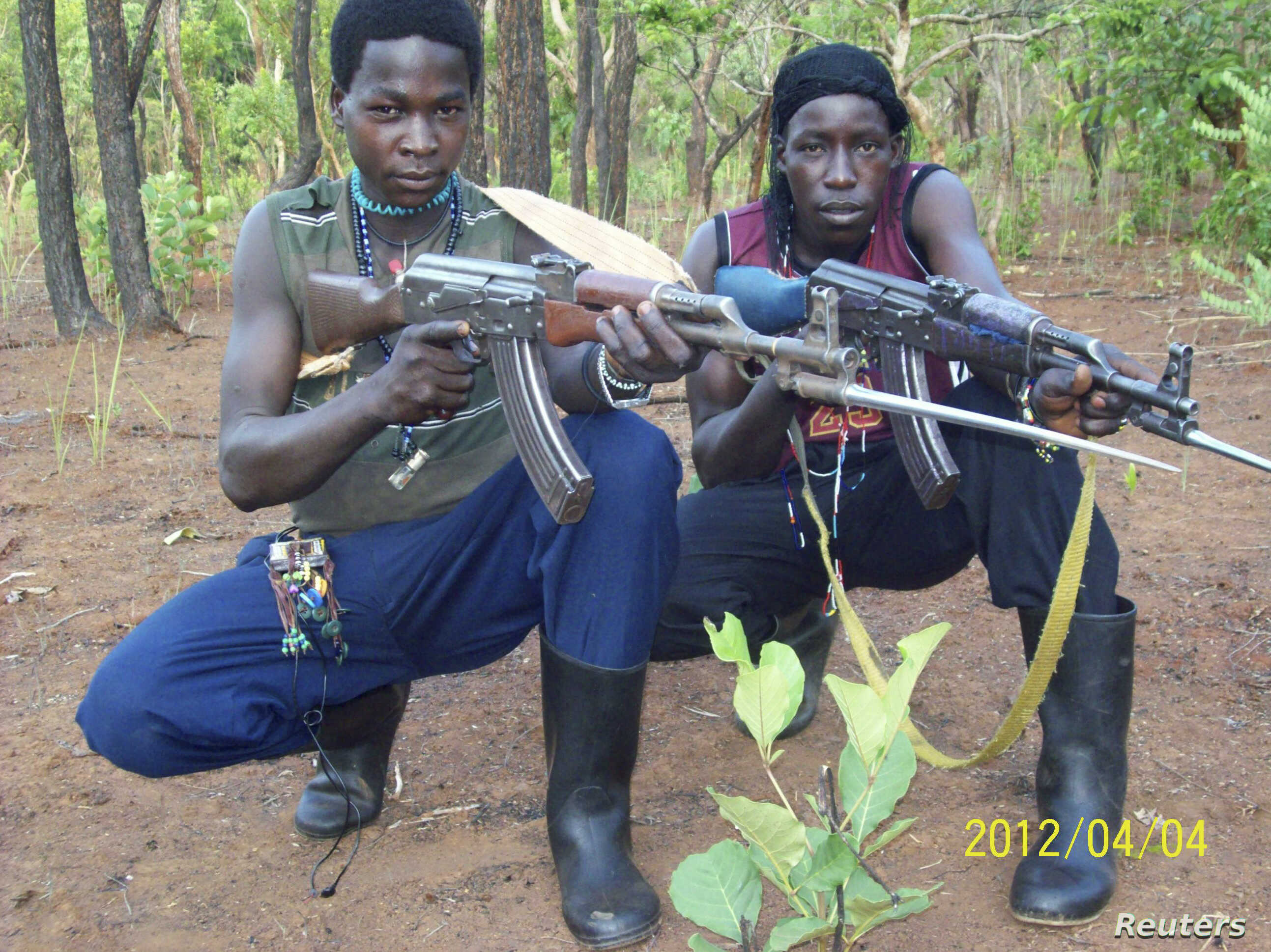 FILE - Fighters loyal to the Lord's Resistance Army pose with their rifles inside the forest near River Mbou in the Central African Republic in this handout picture dated April 4, 2012.