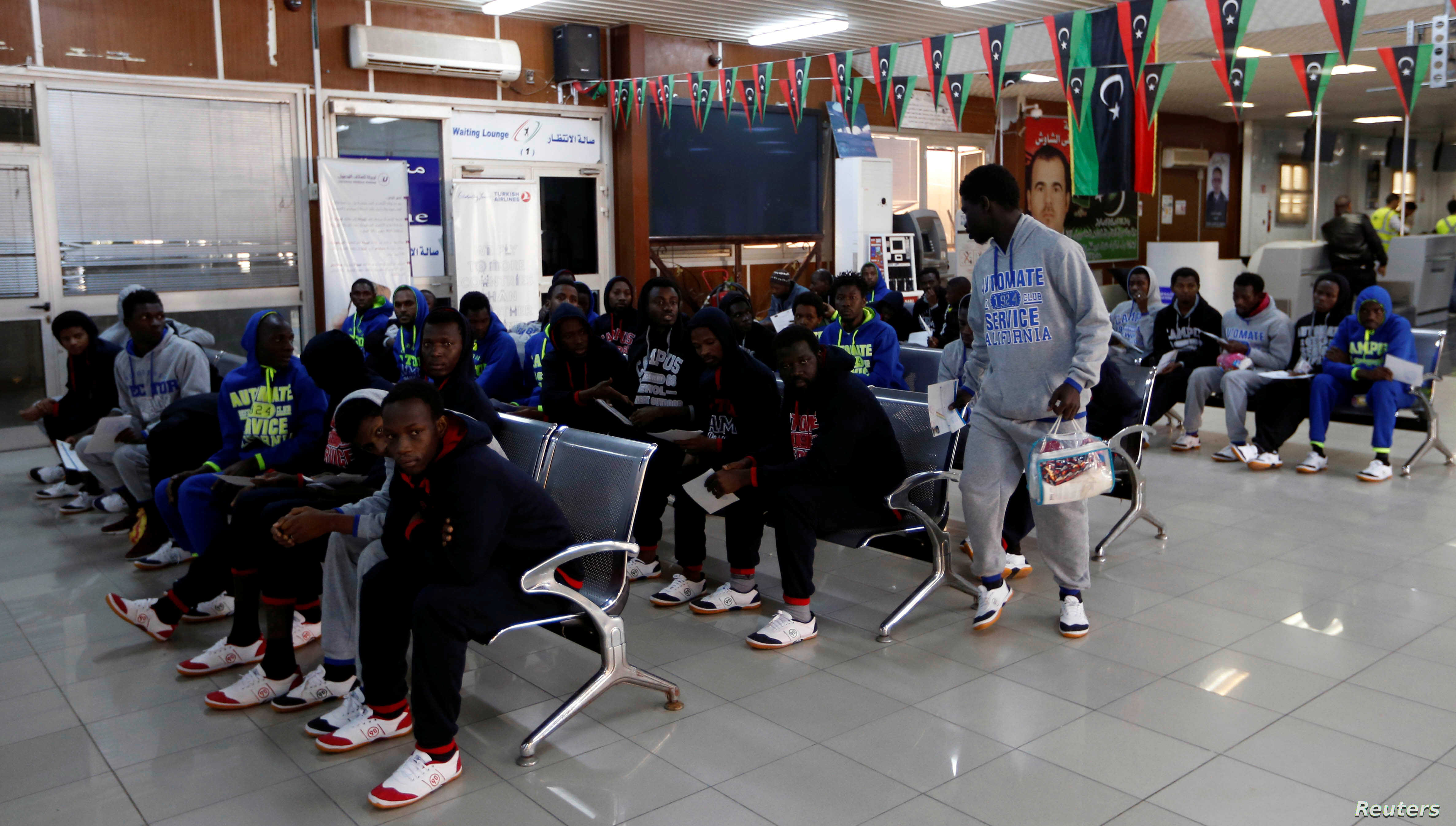Guinean migrants wait at the airport before being deported to Guinea, in Misrata, Libya, Dec. 27, 2017.