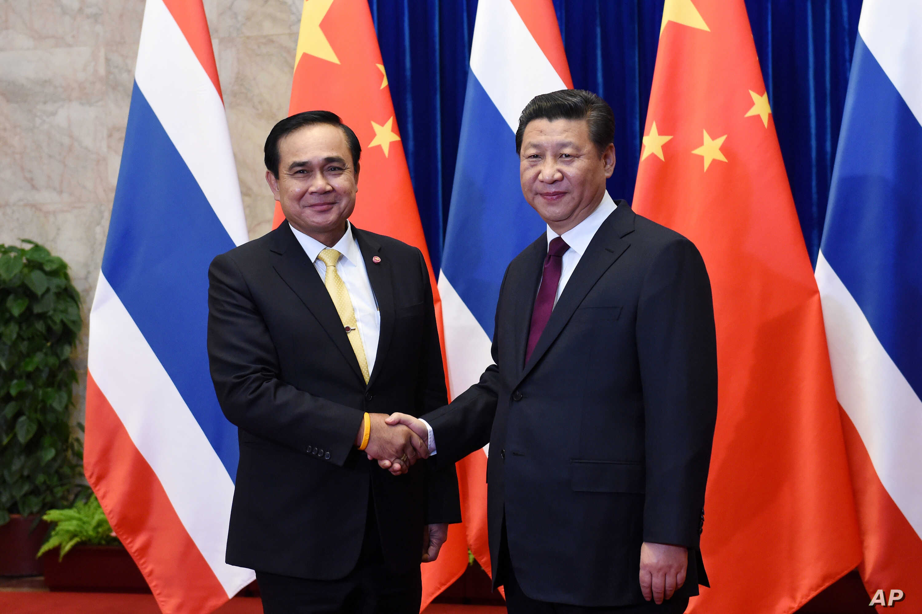 FILE - Thai Prime Minister Prayut Chan-ocha, left,  shakes hands with Chinese President Xi Jinping, right,  before a meeting at the Great Hall of the People in Beijing, Dec. 23, 2014.