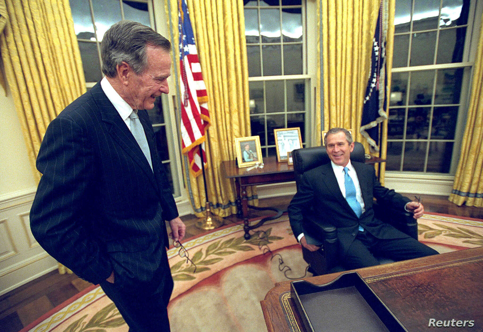 U.S. President George W. Bush sits at his desk in the Oval Office for the first time on Inaugural Day, in this January 20, 2001 file photo, as his father, former President George H.W. Bush looks on.
