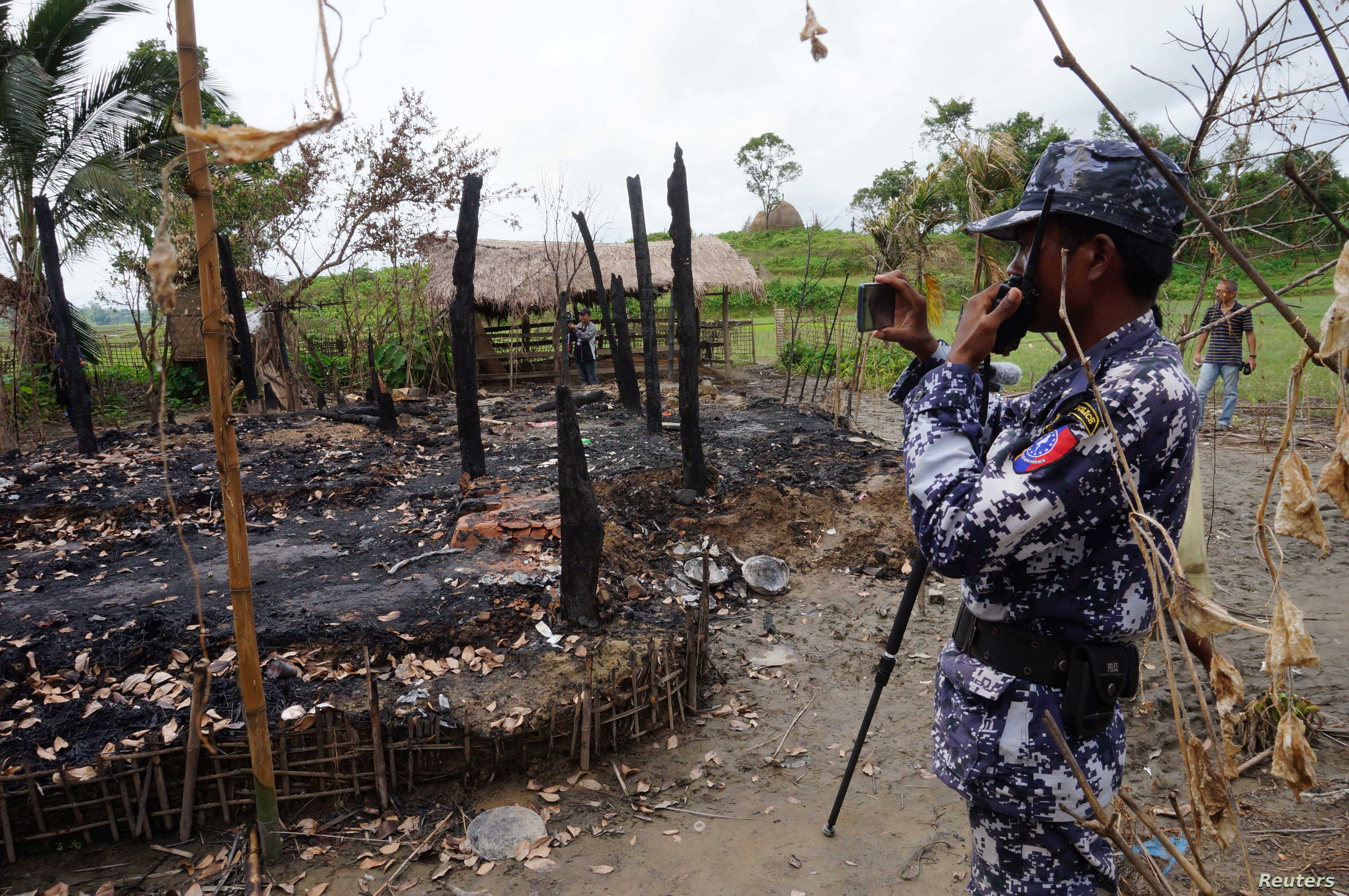 FILE - A Myanmar border guard police officer takes pictures at the remains of a burned house in Tin May village, northern Rakhine state, Myanmar.