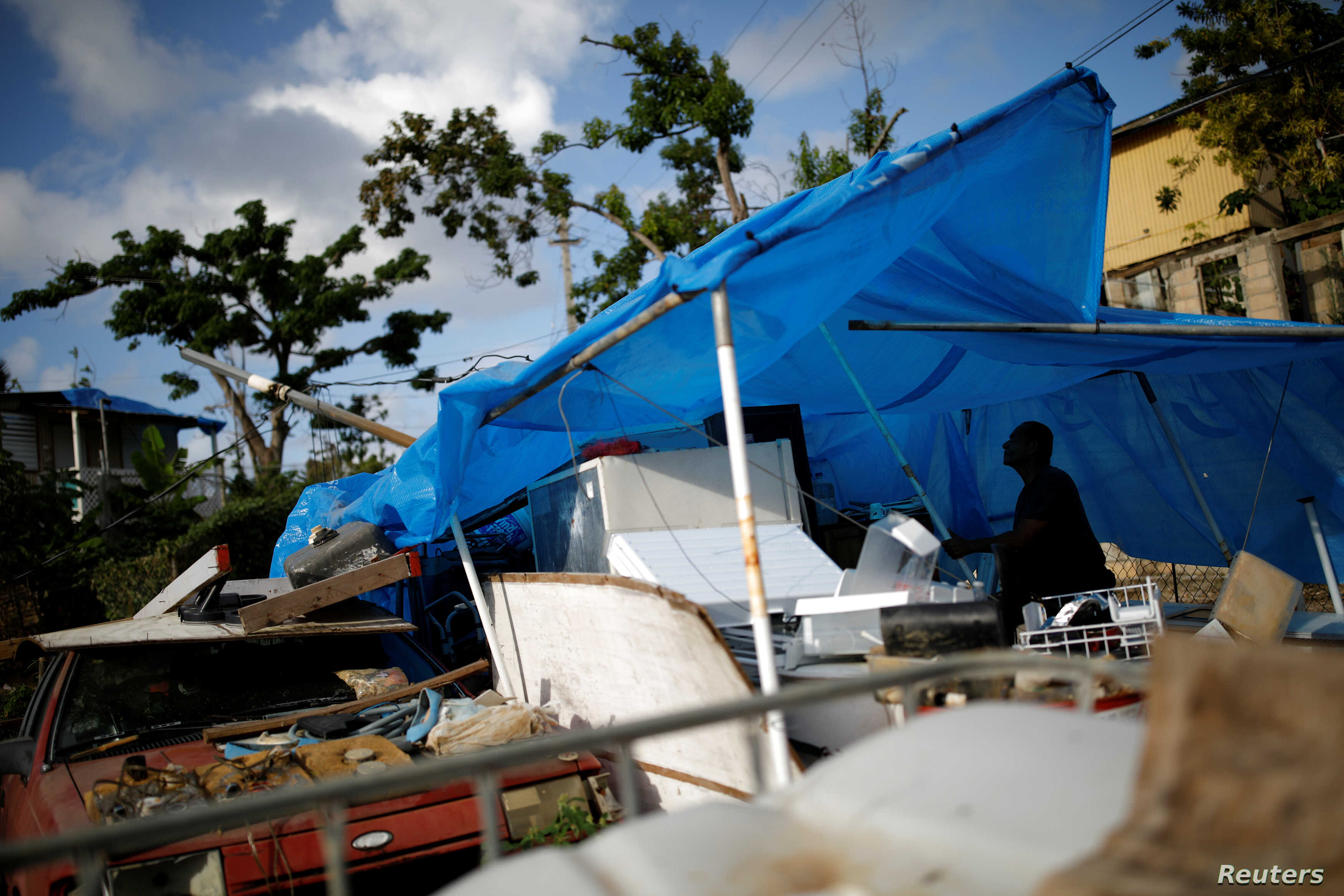 FILE - Joe Quirindongo tries to repair a makeshift tent where he keeps some belongings at the squatter community of Villa Hugo in Canovanas, Puerto Rico, Dec. 9, 2017.