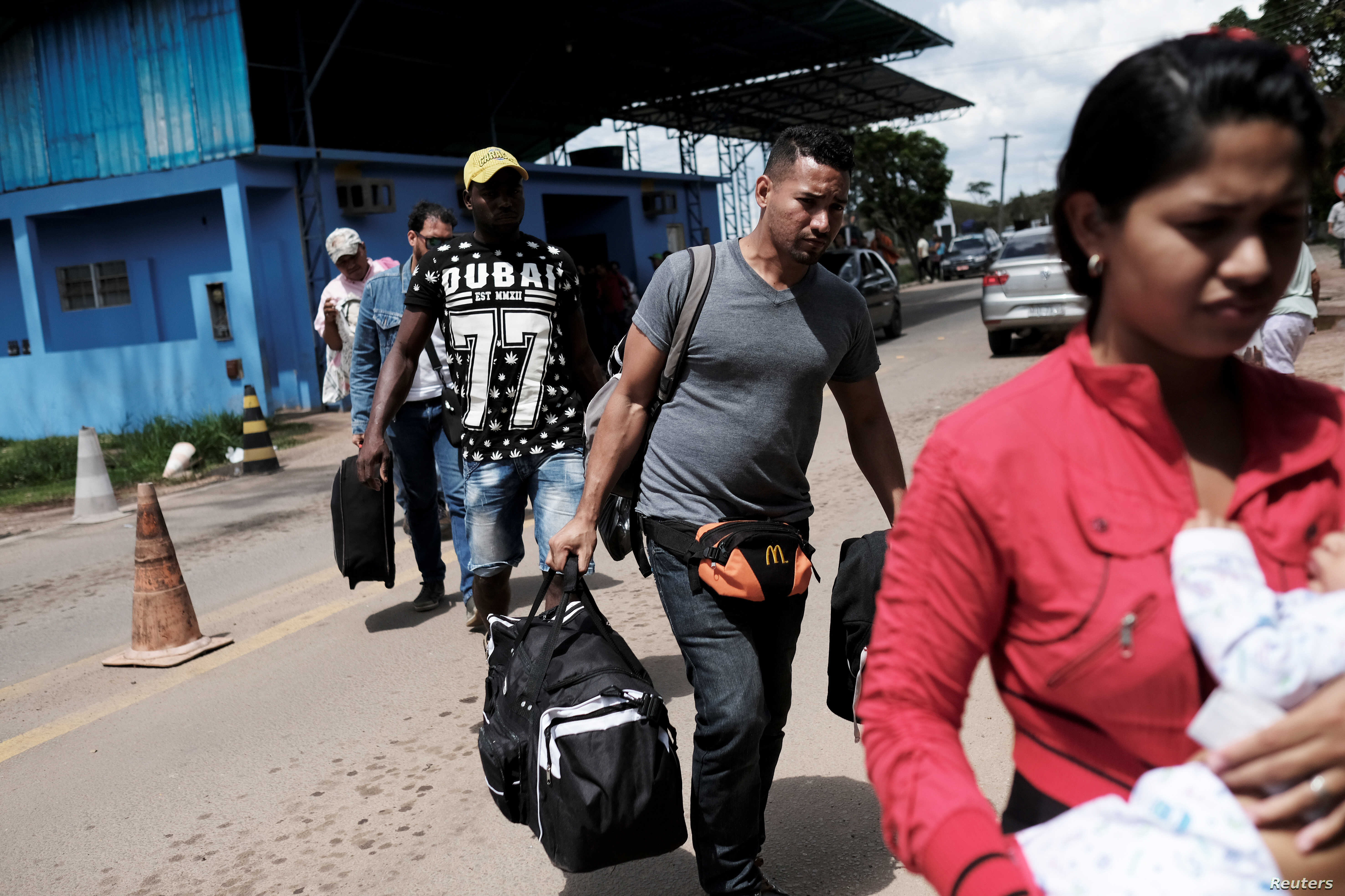 Venezuelans walk to show their passports or identity cards at the Pacaraima border control, Roraima state, Brazil Nov. 16, 2017. The border control is manned by Federal Police only during the day.