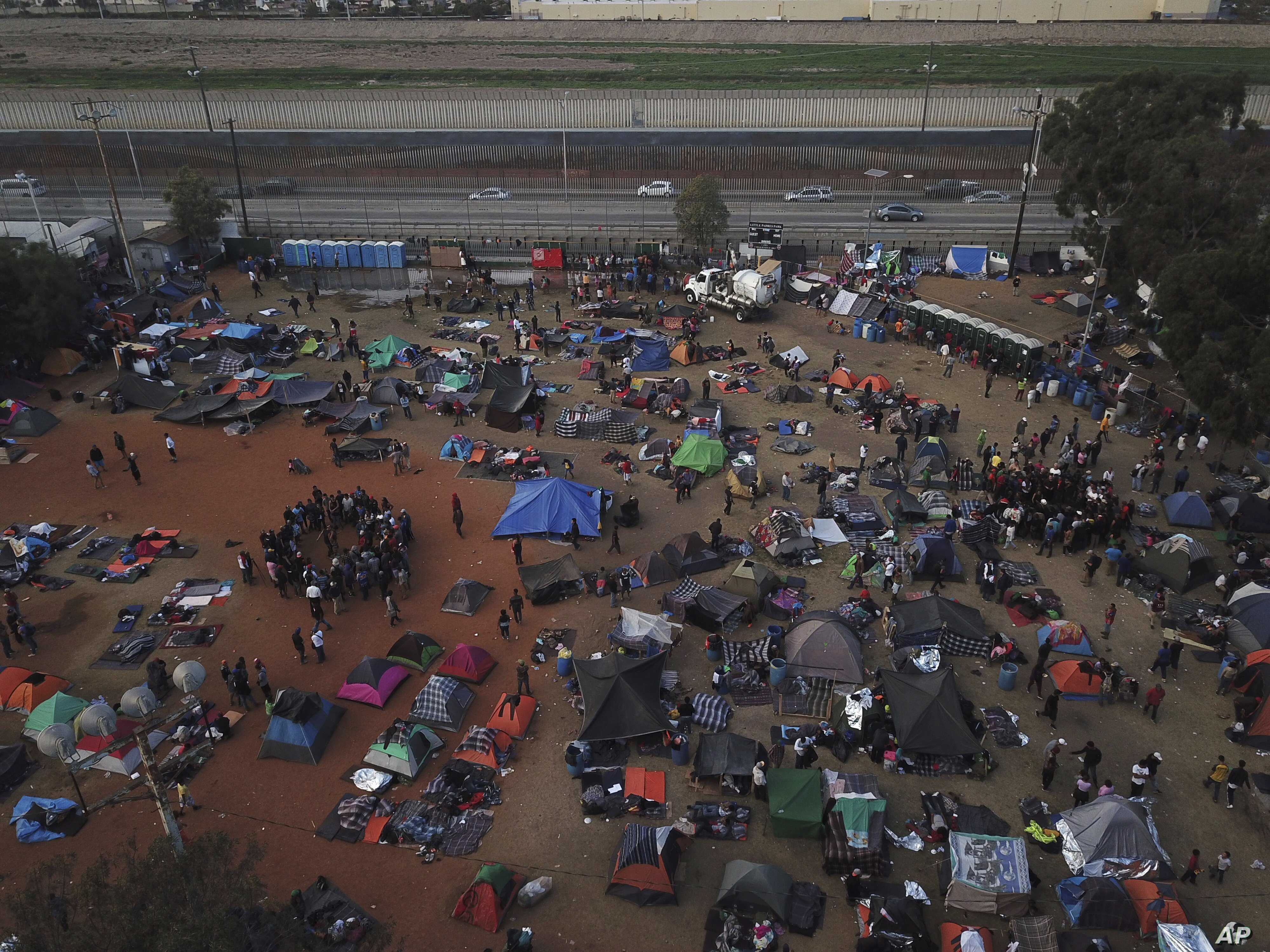 Central American migrants gather at a temporary shelter, near barriers that separate Mexico and the United States, in Tijuana, Mexico, Nov. 21, 2018.