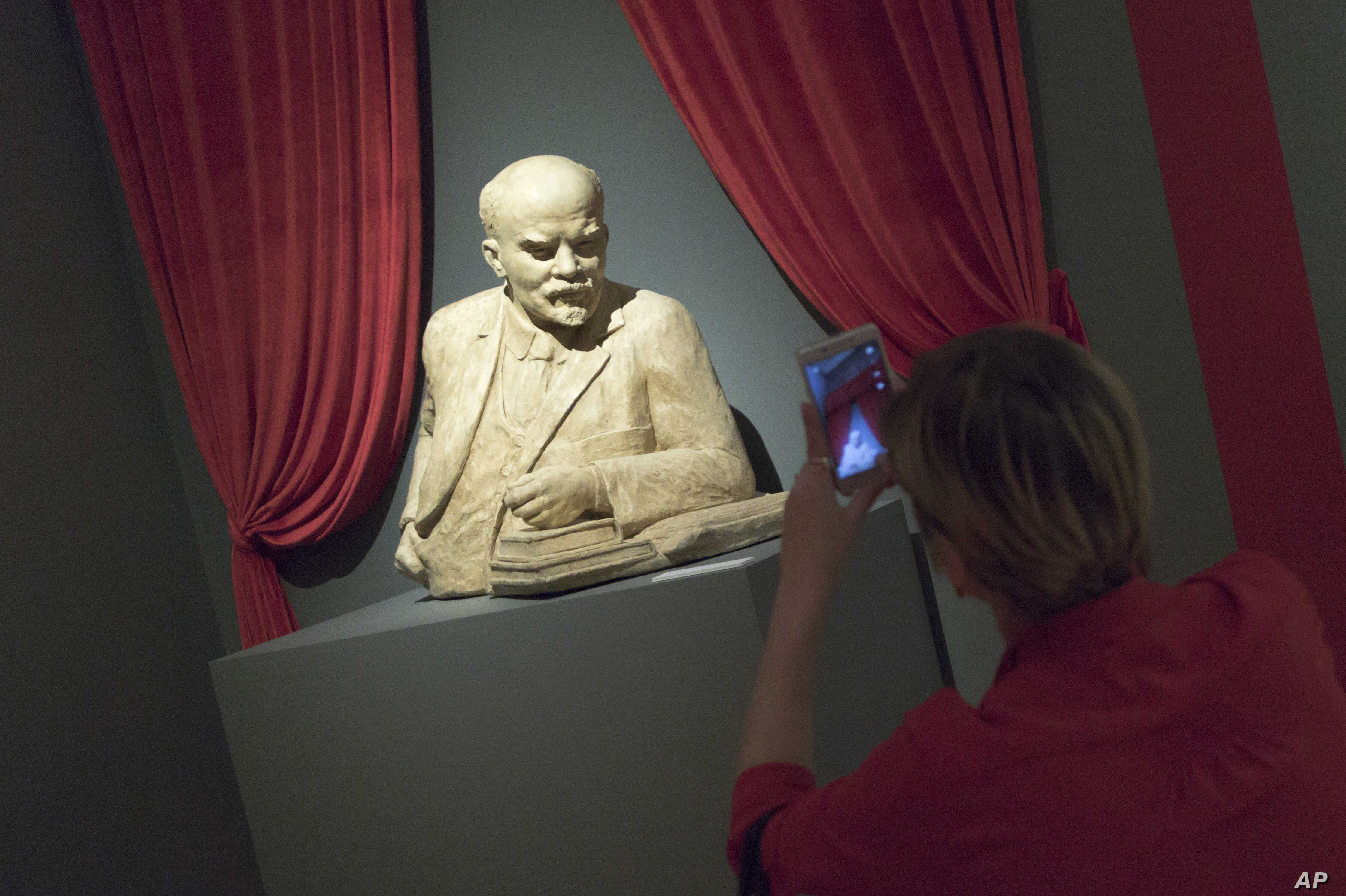 "A woman photographs the sculpture of Soviet founder Vladimir Lenin during the opening of ""Energy of the Dream. Ð¡entennial of the 1917 Revolution"" exhibition in Moscow, Nov. 2, 2017."