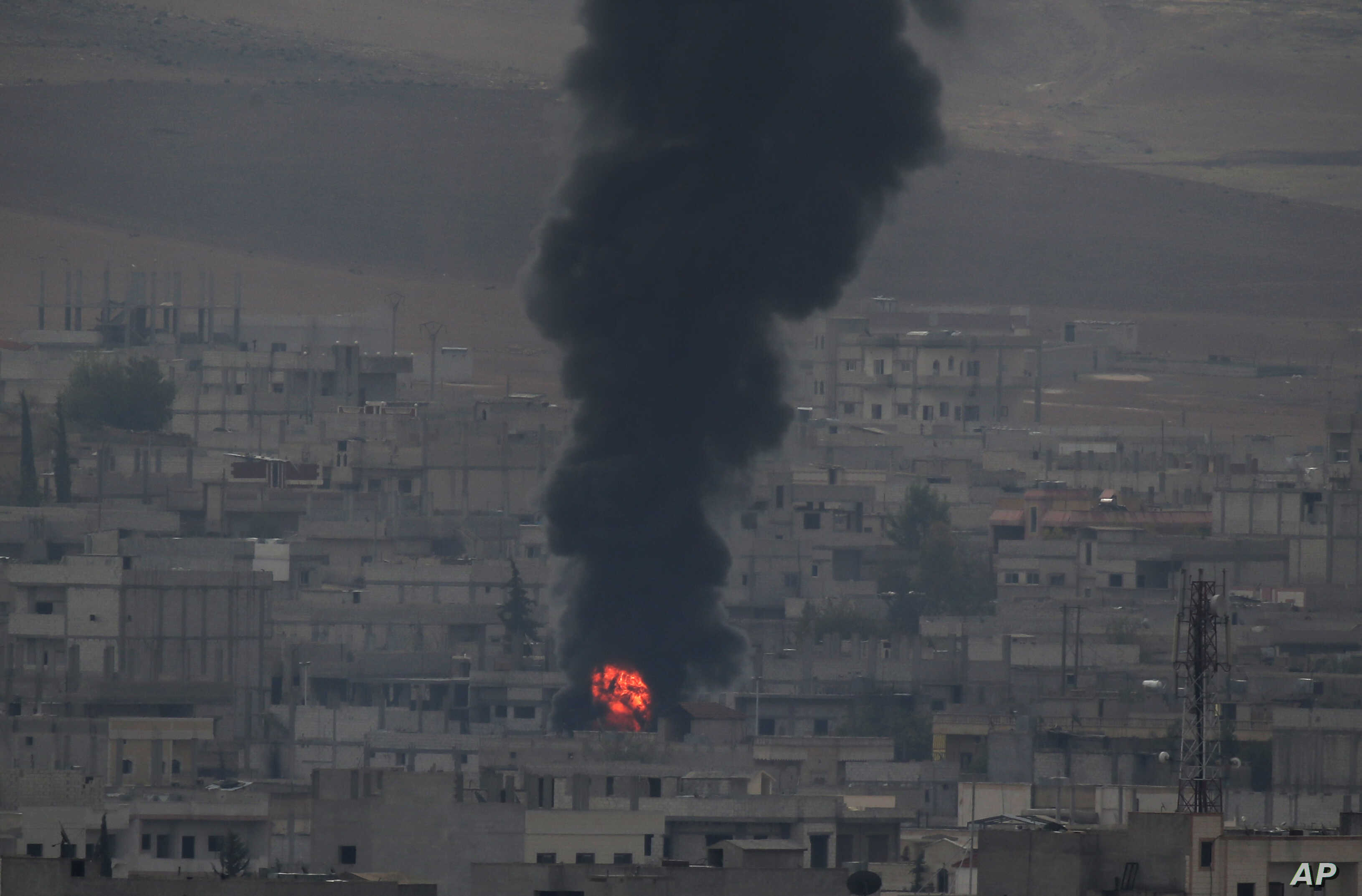 Thick smoke and flames from a fire rises following a strike in Kobani, Syria, during fighting between Syrian Kurds and the militants of the Islamic State group, as seen from a hilltop on the outskirts of Suruc, at the Turkey-Syria border, Oct. 19, 20...