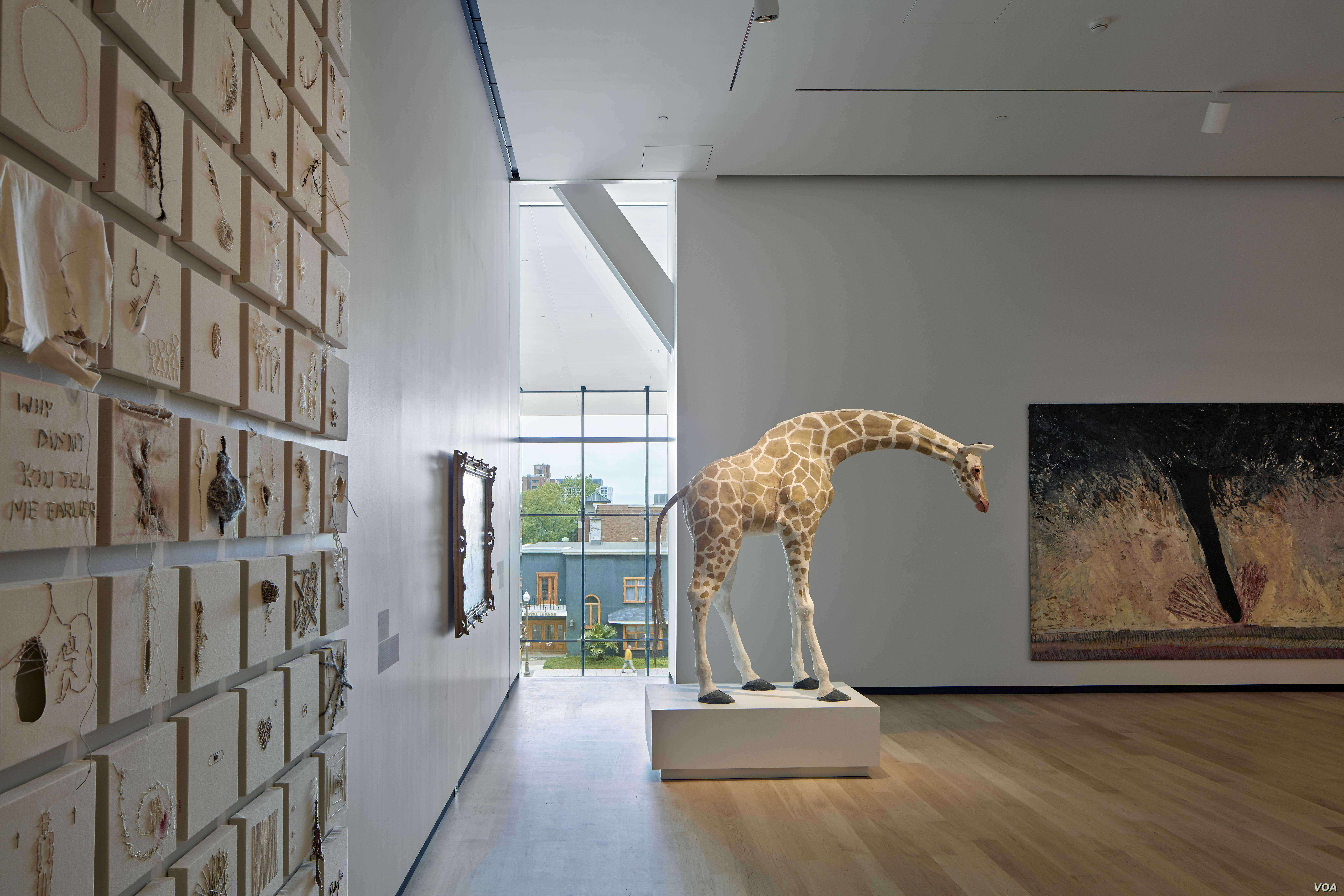 Part of Nadia Myre's The Scar can be seen on the far left. In the center is Trevor Gould's Nubian Giraffe. Through the window, visitors can look out onto Quebec's Grand Allee and the city beyond.