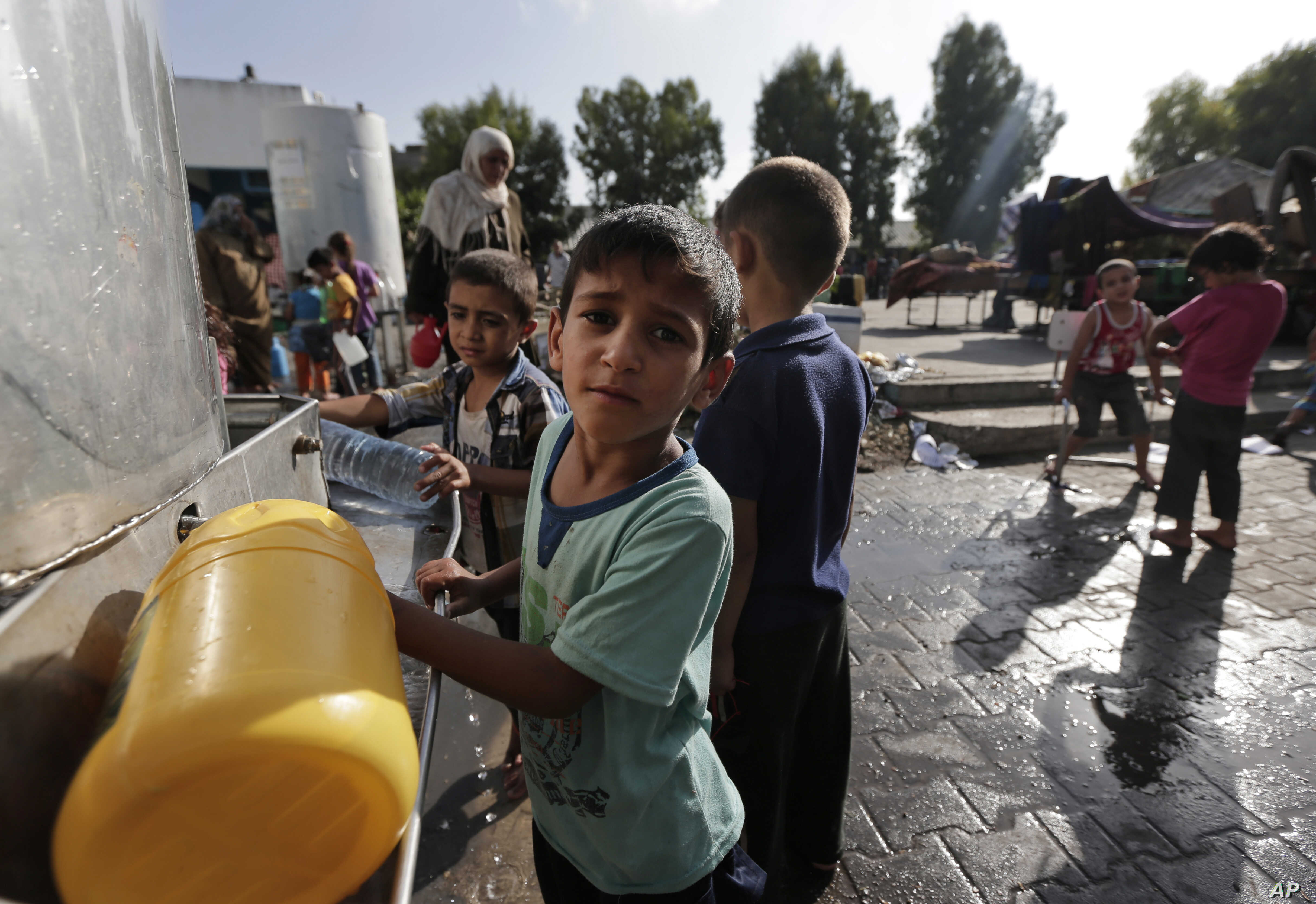 Displaced Palestinian children collect water at the Abu Hussein U.N. school in Jebaliya refugee camp, northern Gaza Strip, on July 30, 2014. It had been hit by artillery shells earlier in the day.