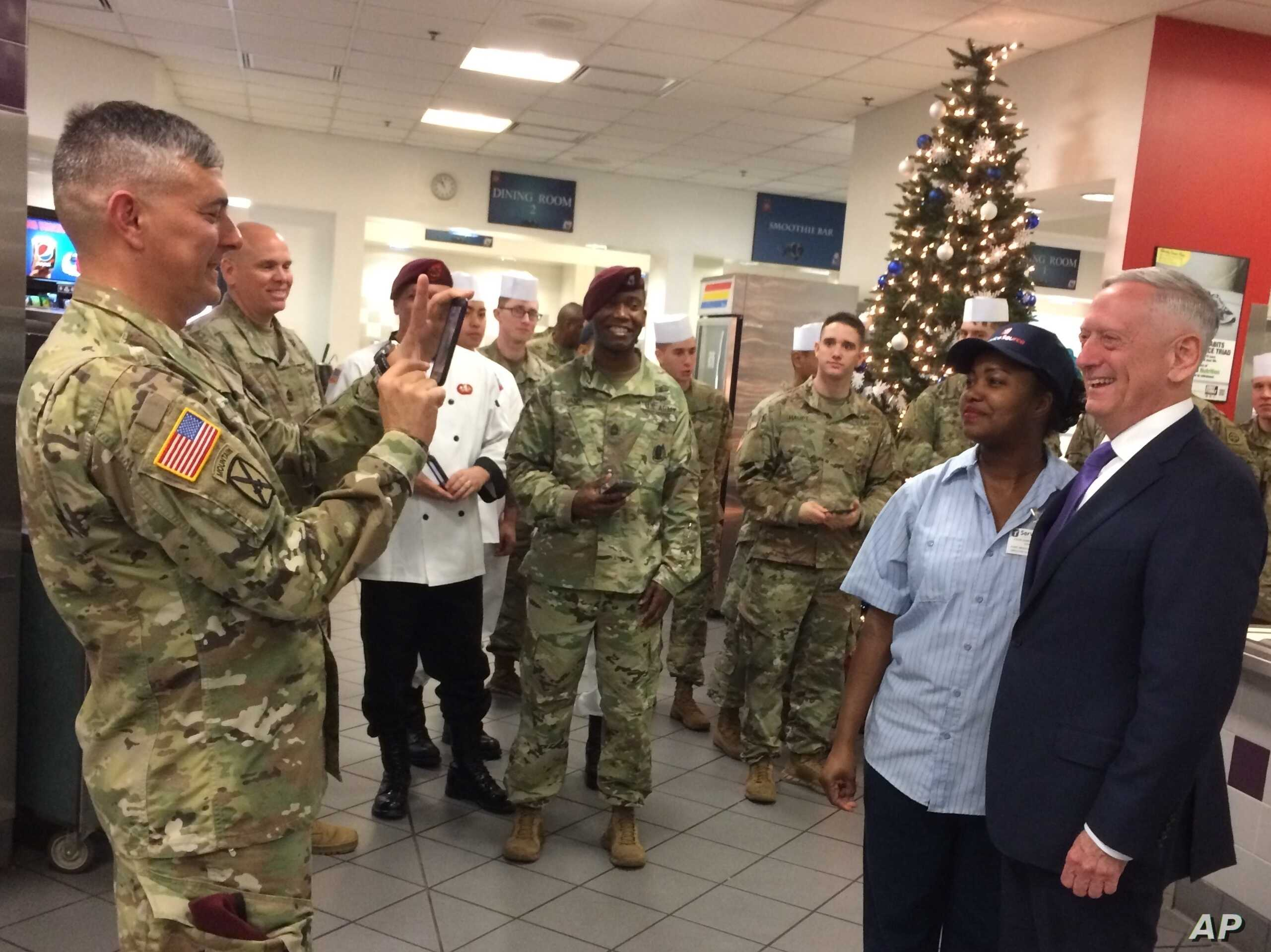 FILE - Lt. Gen. Stephen Townsend takes a photo of Defense Secretary Jim Mattis and a dining facility worker at Fort Bragg, N.C., Dec. 22, 2017.