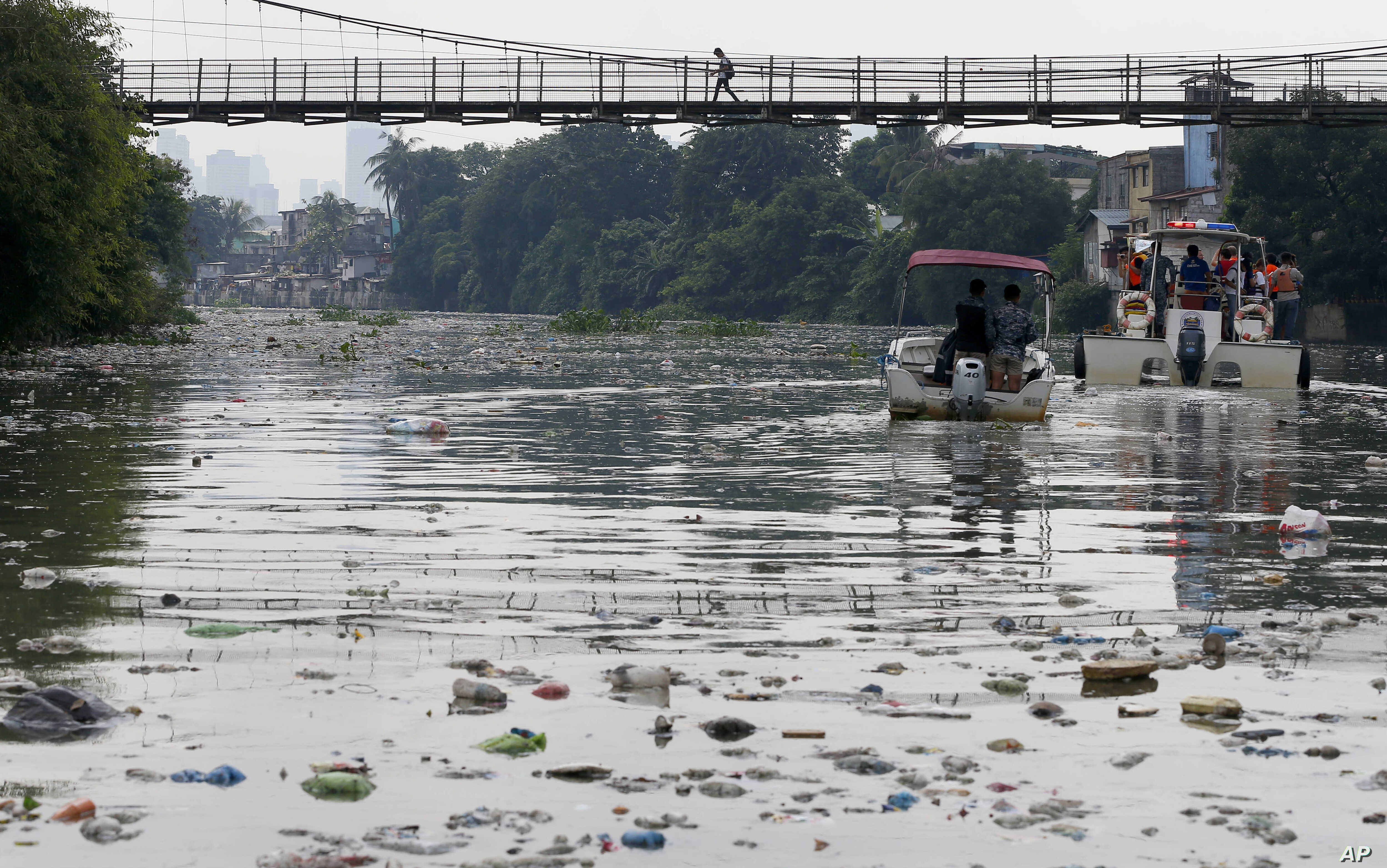 FILE - The Government's Pasig River Rehabilitation Commission and environmentalists from Greenpeace survey the polluted Pasig River to track plastic waste to draw attention to the hazards of plastics and waste which clog rivers and tributaries in San...