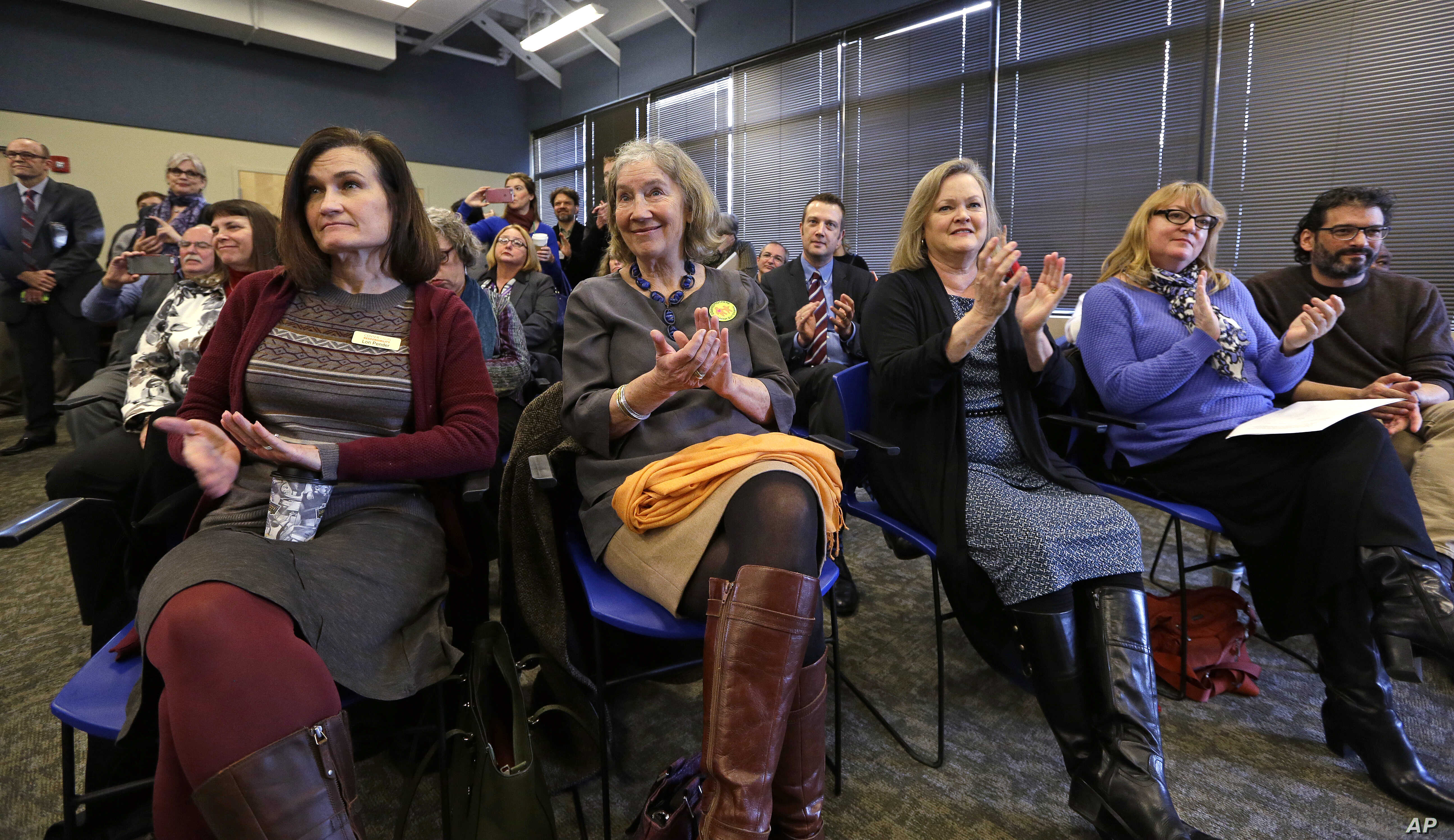 Center for Gun Responsibility board members applaud at a news conference in Burien, Wash., where Gov. Jay Inslee announced a statewide public health initiative to reduce and prevent firearm-related injuries and deaths, Jan. 6, 2016.