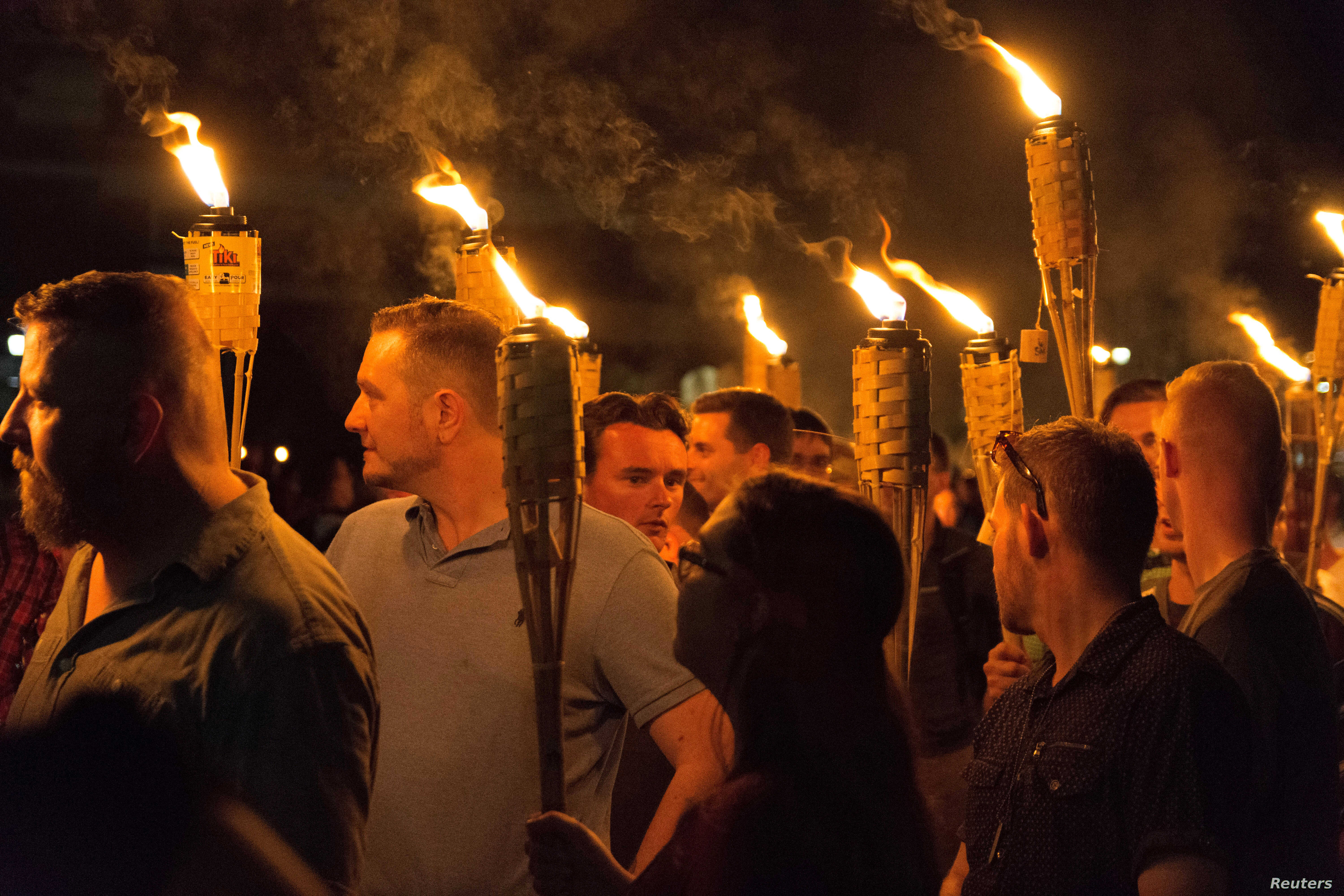 """White supremacists carry torches on the grounds of the University of Virginia, on the eve of a planned """"Unite the Right"""" rally in Charlottesville, Virginia, Aug. 11, 2017."""