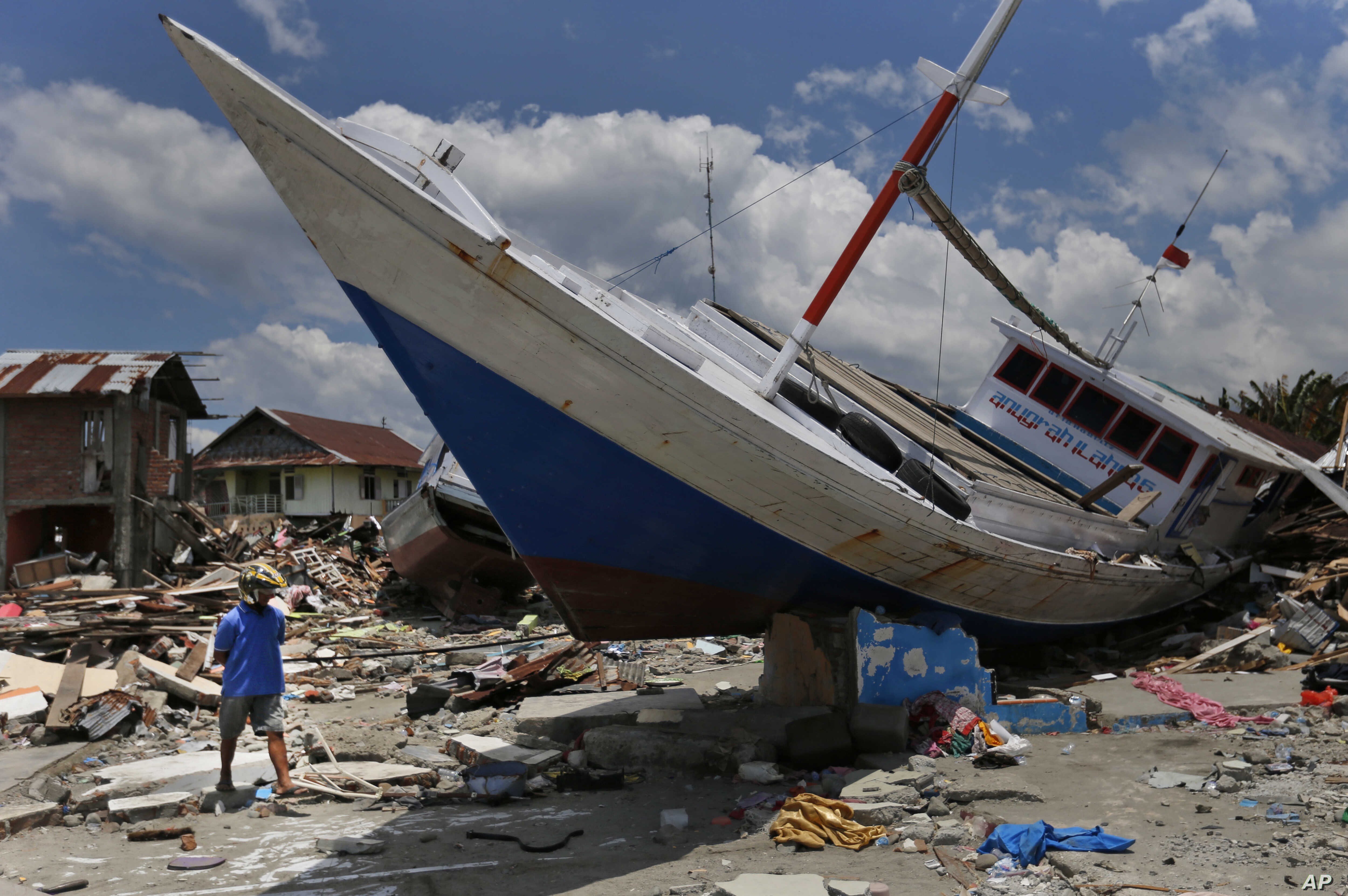 A man walks past a boat swept ashore by a tsunami in Wani village on the outskirt of Palu, Central Sulawesi, Indonesia, Wednesday, Oct. 10, 2018.