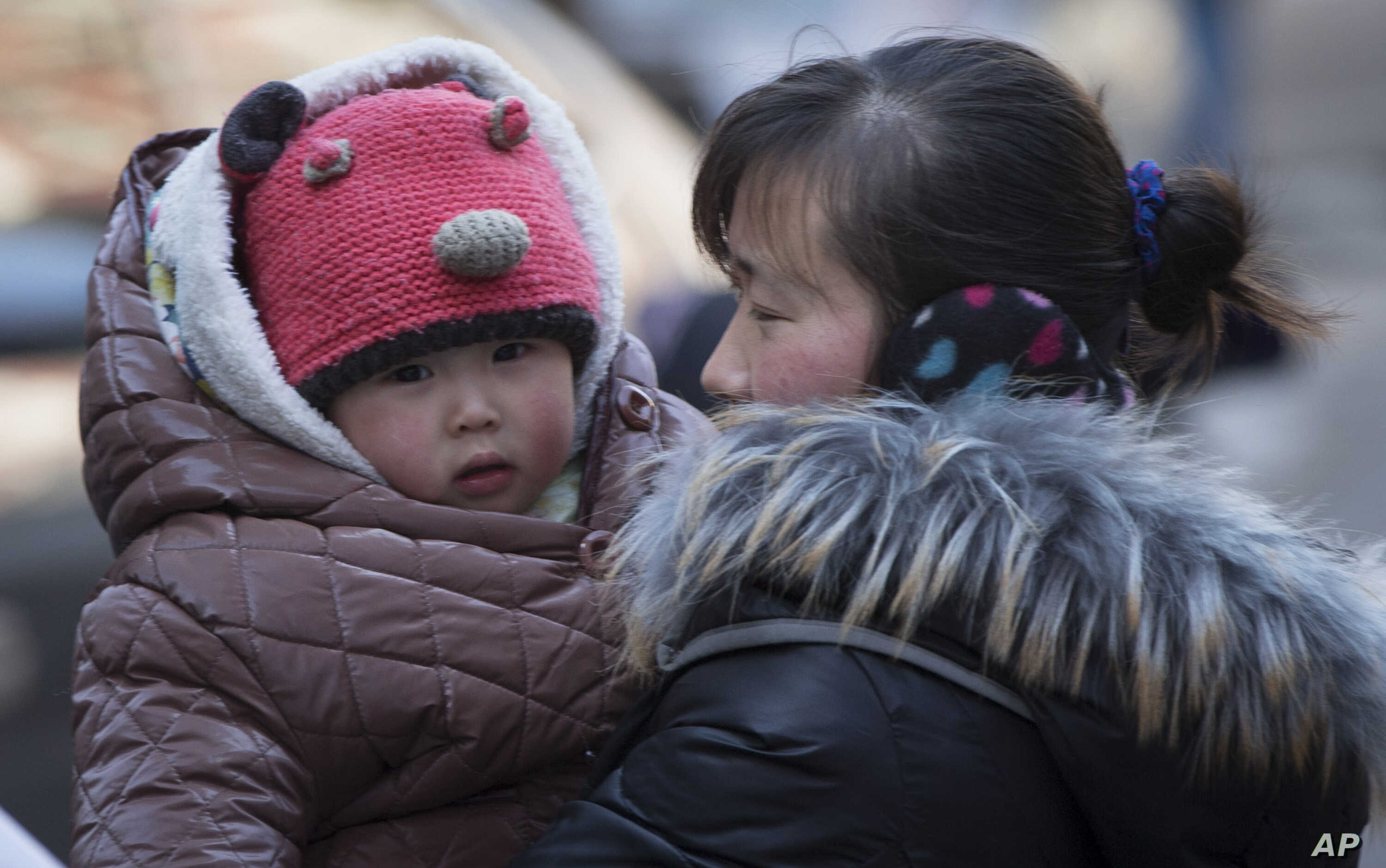 FILE - A Chinese woman cuddles her child in Beijing, China, March 6, 2014. China announced Thursday it was ending its long-standing one-child policy and will now allow all couples to have two children.
