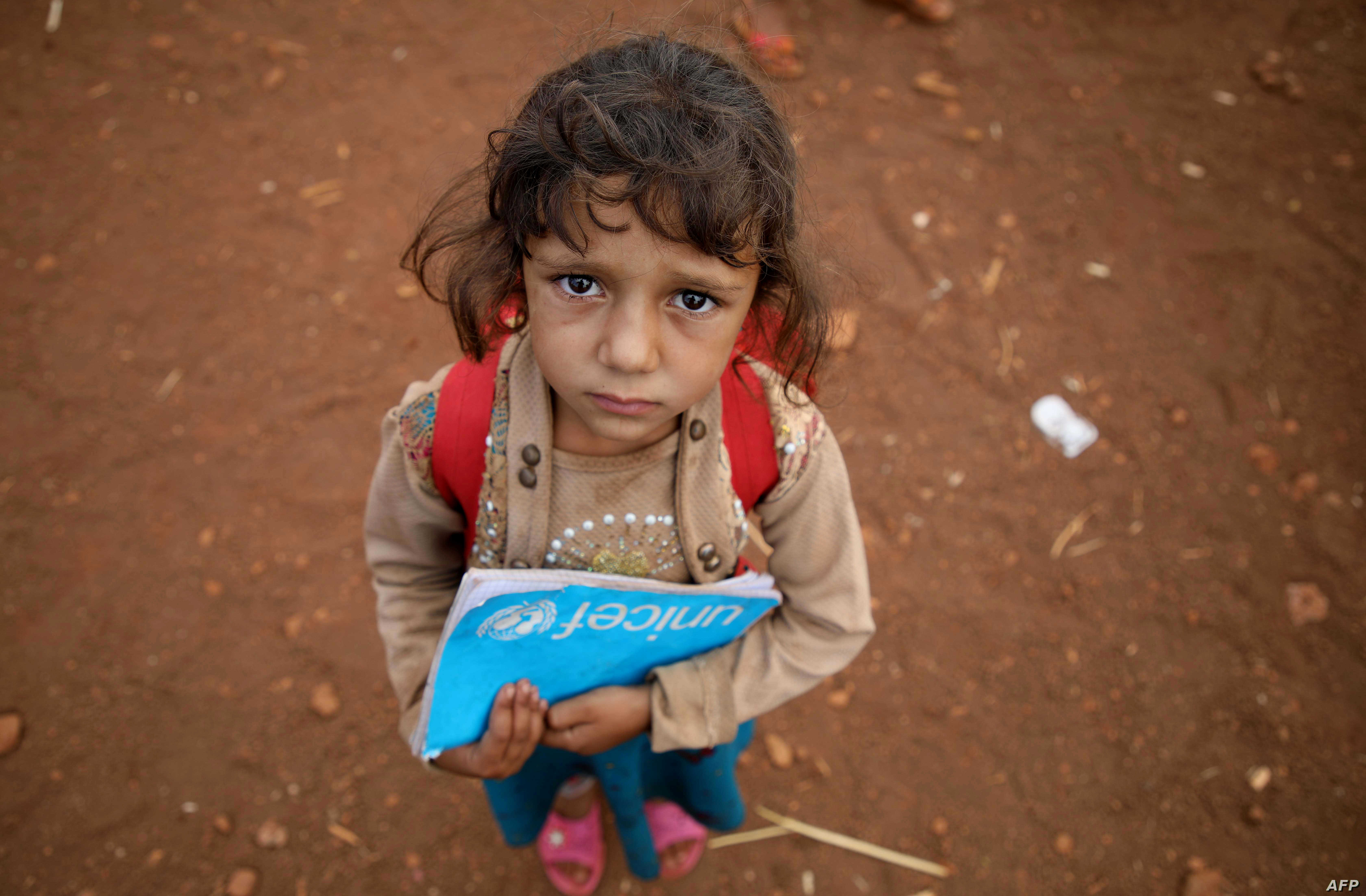 A Syrian child holds a book in the yard of a makeshift school in al-Jeneinah camp for displaced people in the village of Atme, in Syria's mostly rebel-held northern Idlib province.