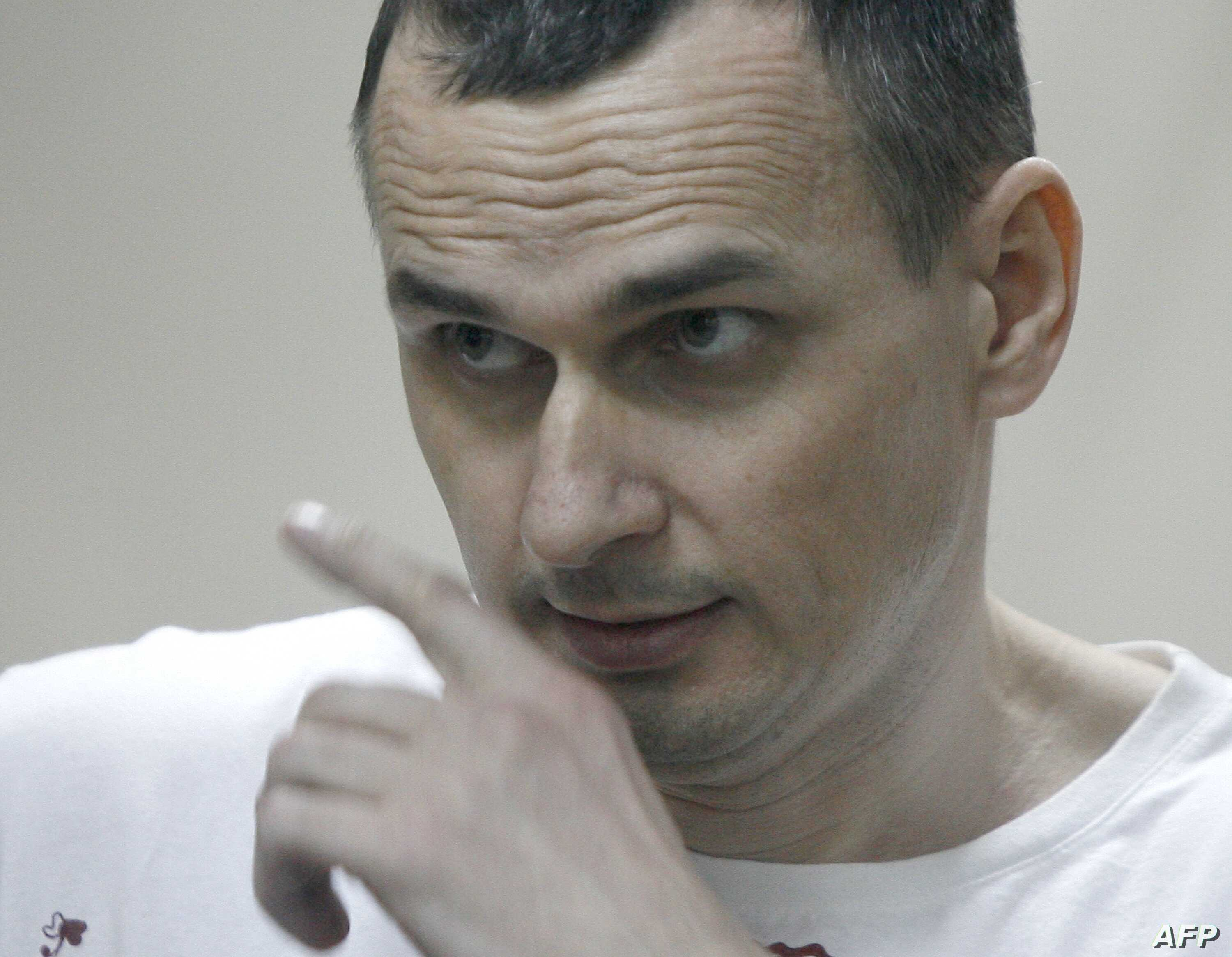 Ukrainian film director Oleg Sentsov looks out from a defendants' cage as he listens to the verdict at a military court in the southern city of Rostov-on-Don, Aug. 25, 2015.